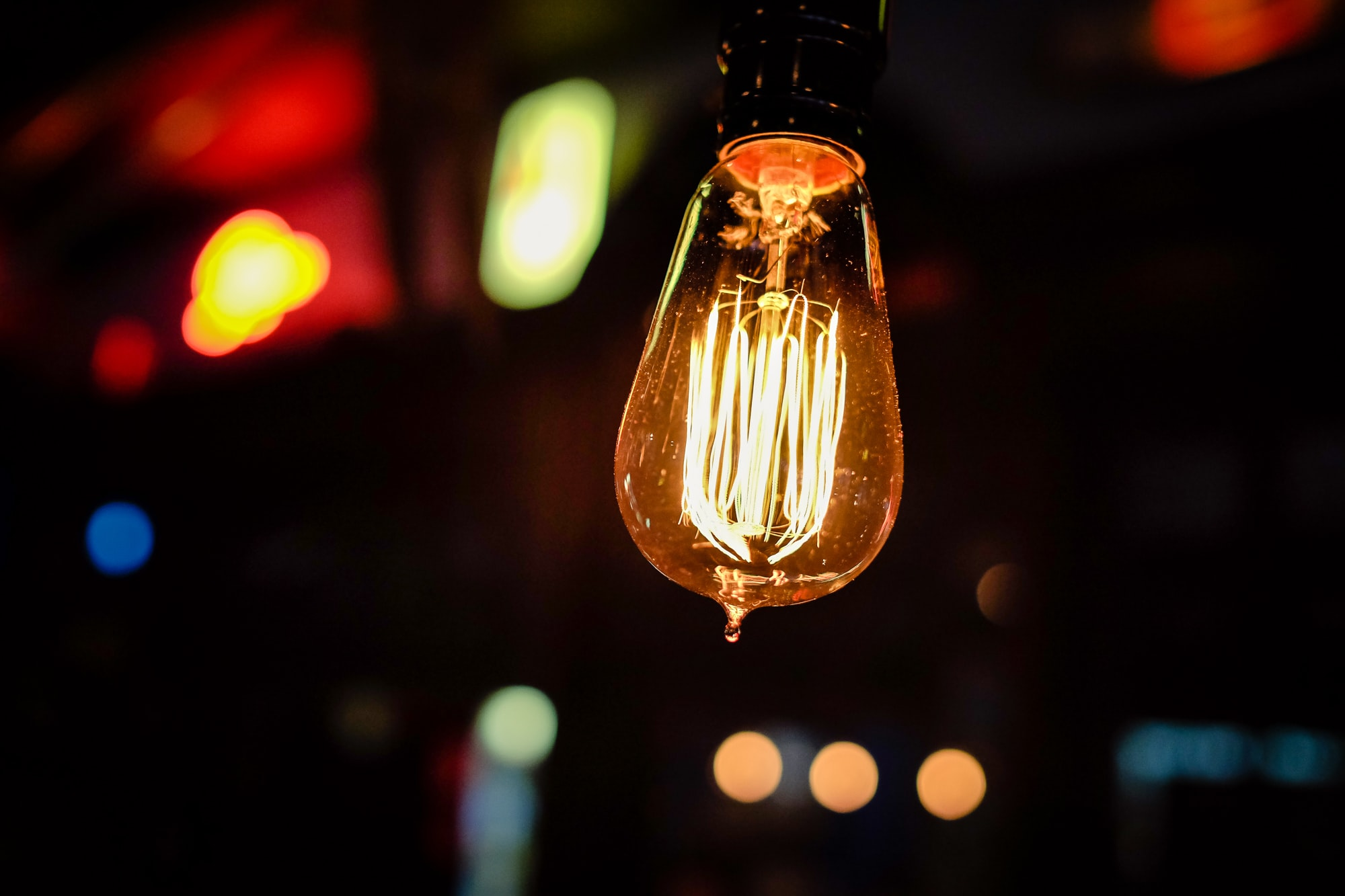 An incandescent light bulb with colorful bokeh lights in the background