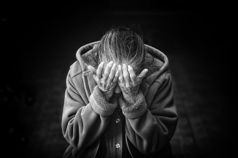 grayscale photography of person covering face