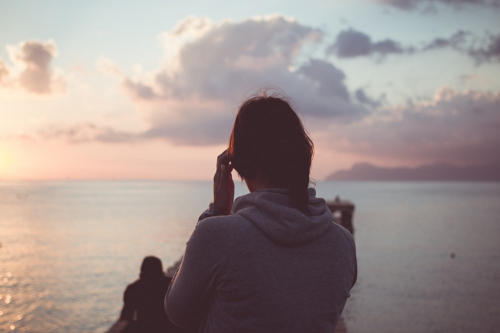 woman in gray hoodie standing at dock