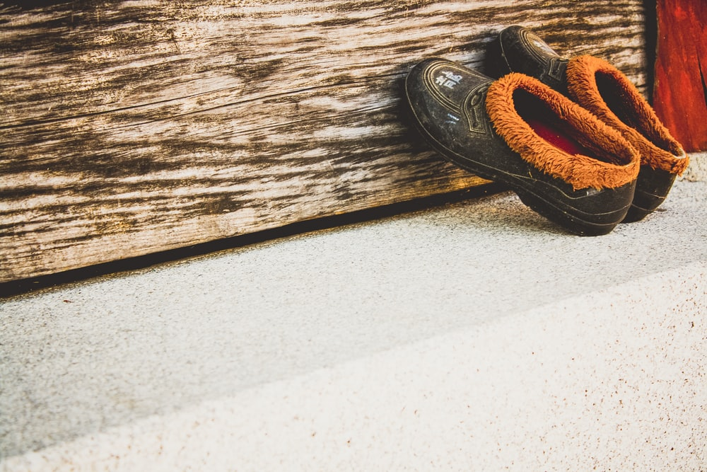 pair of black moccasins shoes leaning on wall