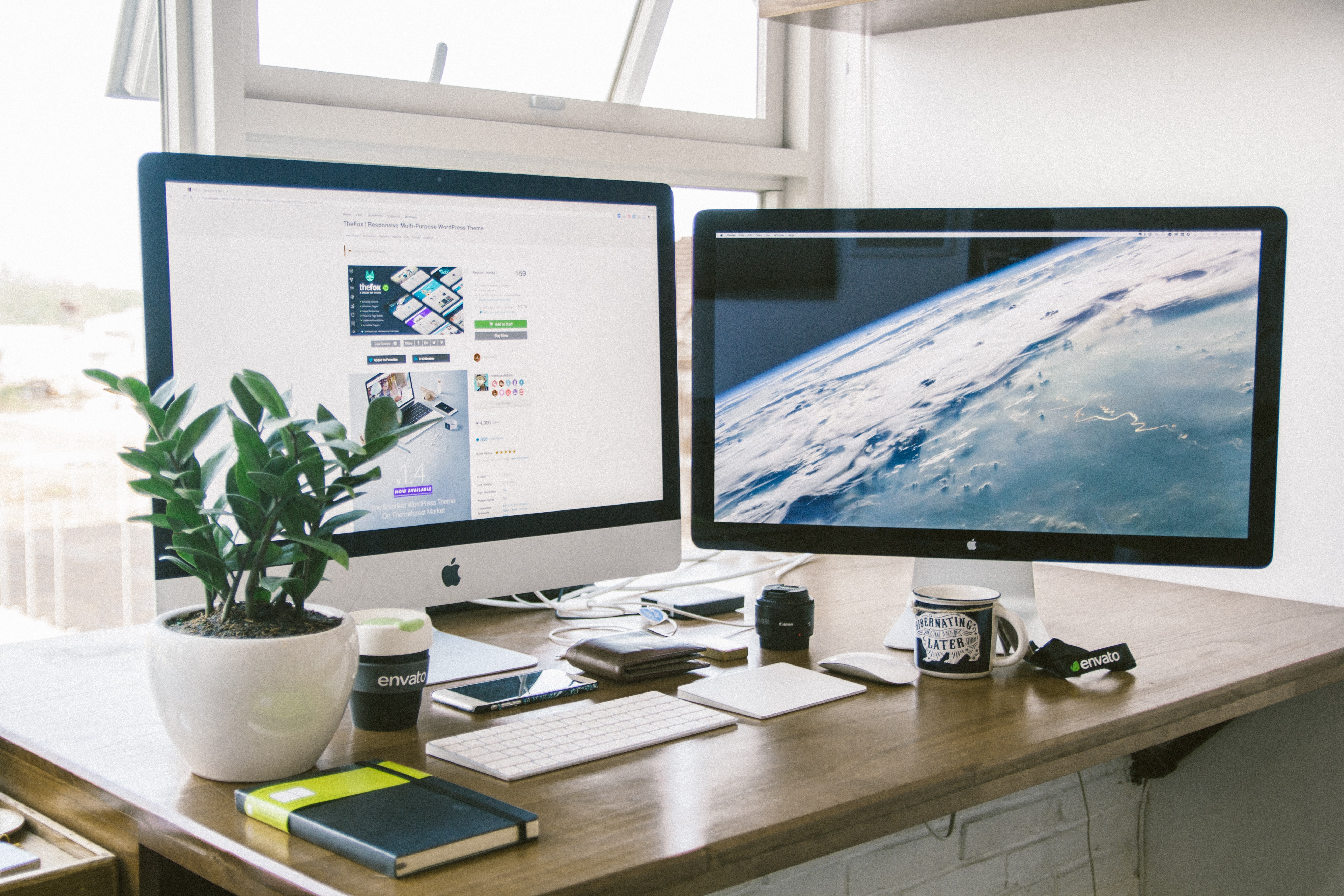 A dual monitor setup on a brown desk.