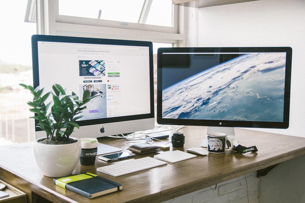 A dual monitor setup on a brown desk.