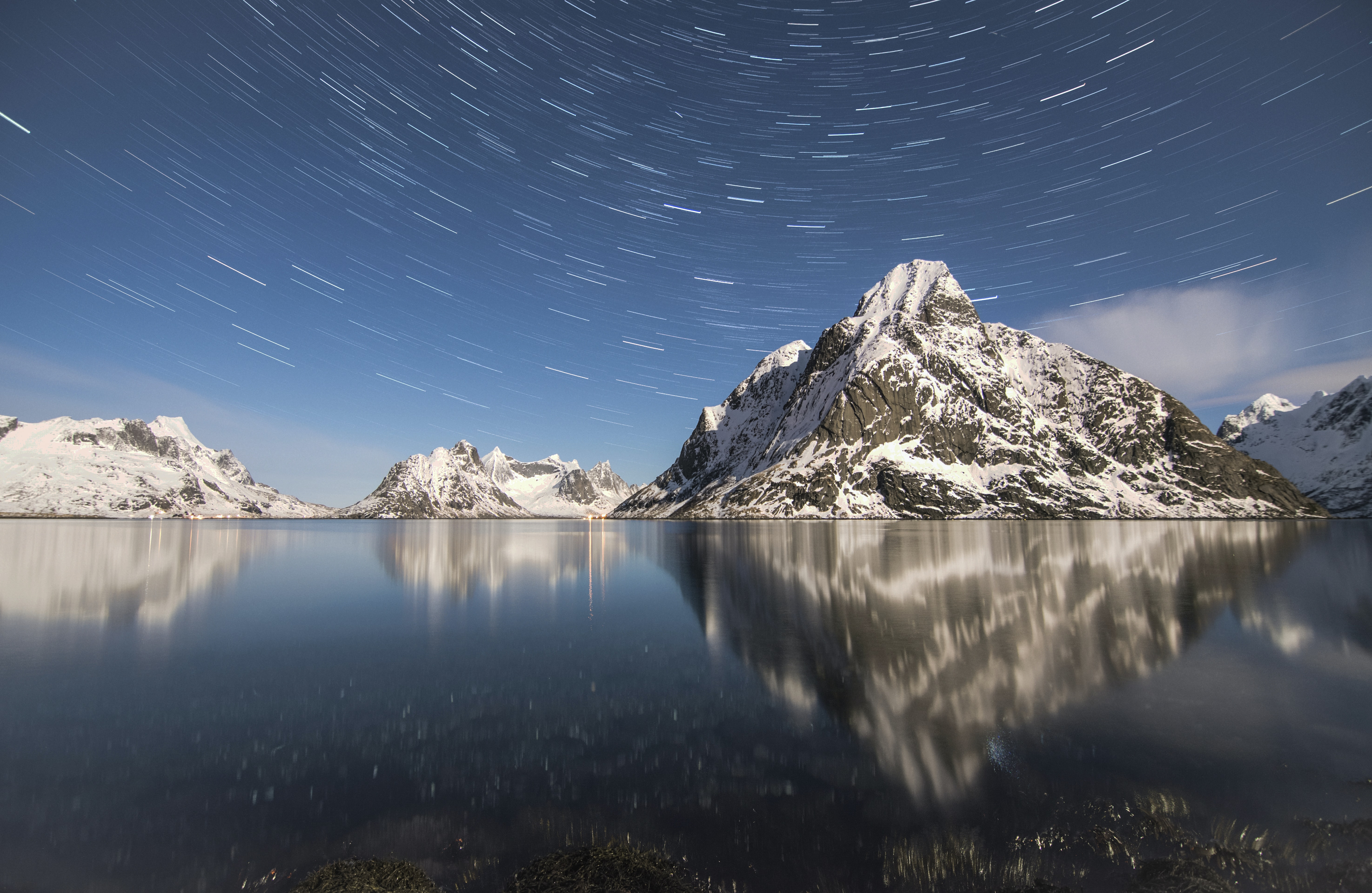 timelapse photography of mountain alps near water with stars