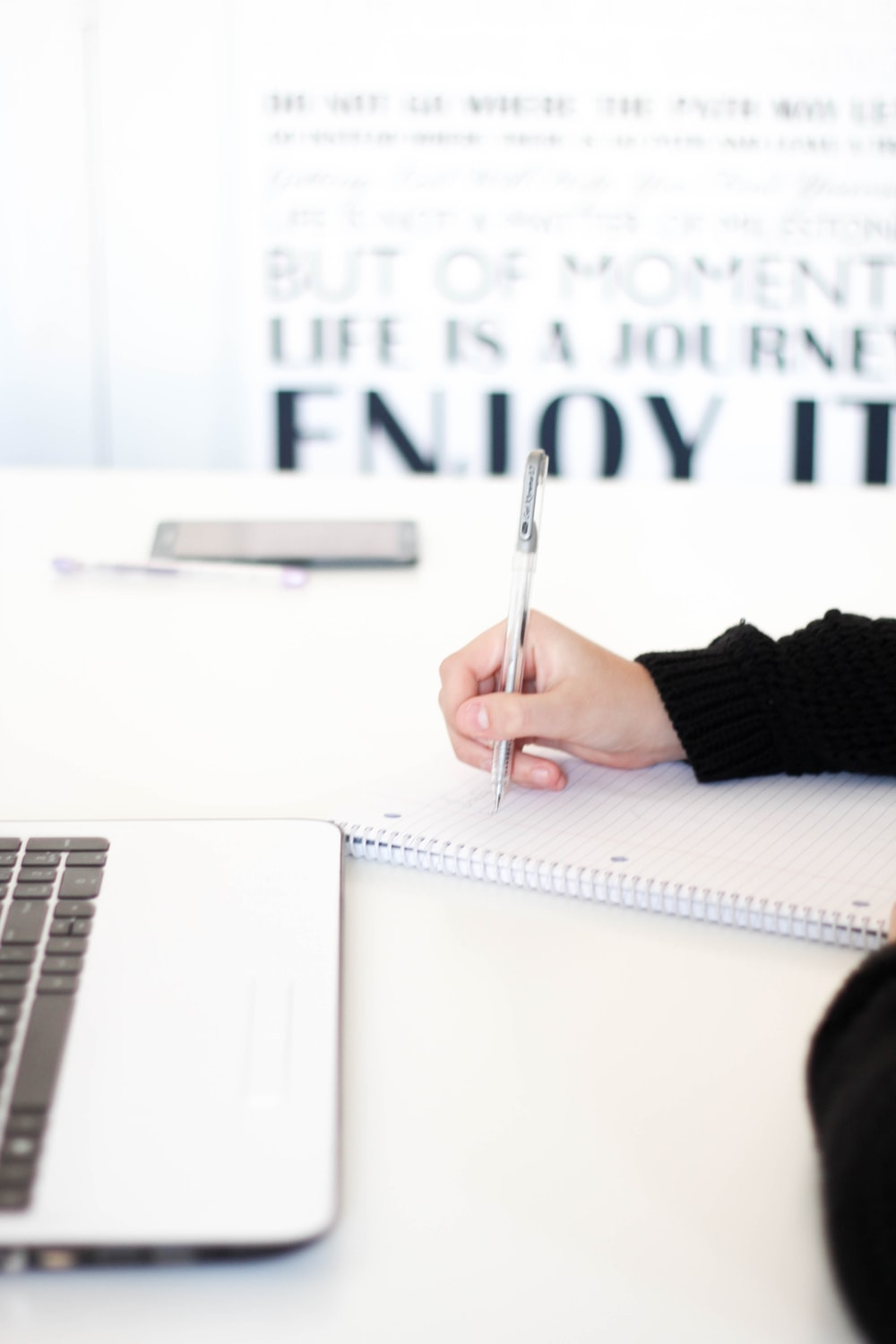 A person writing on a piece of paper, with a motivational quote in the background.