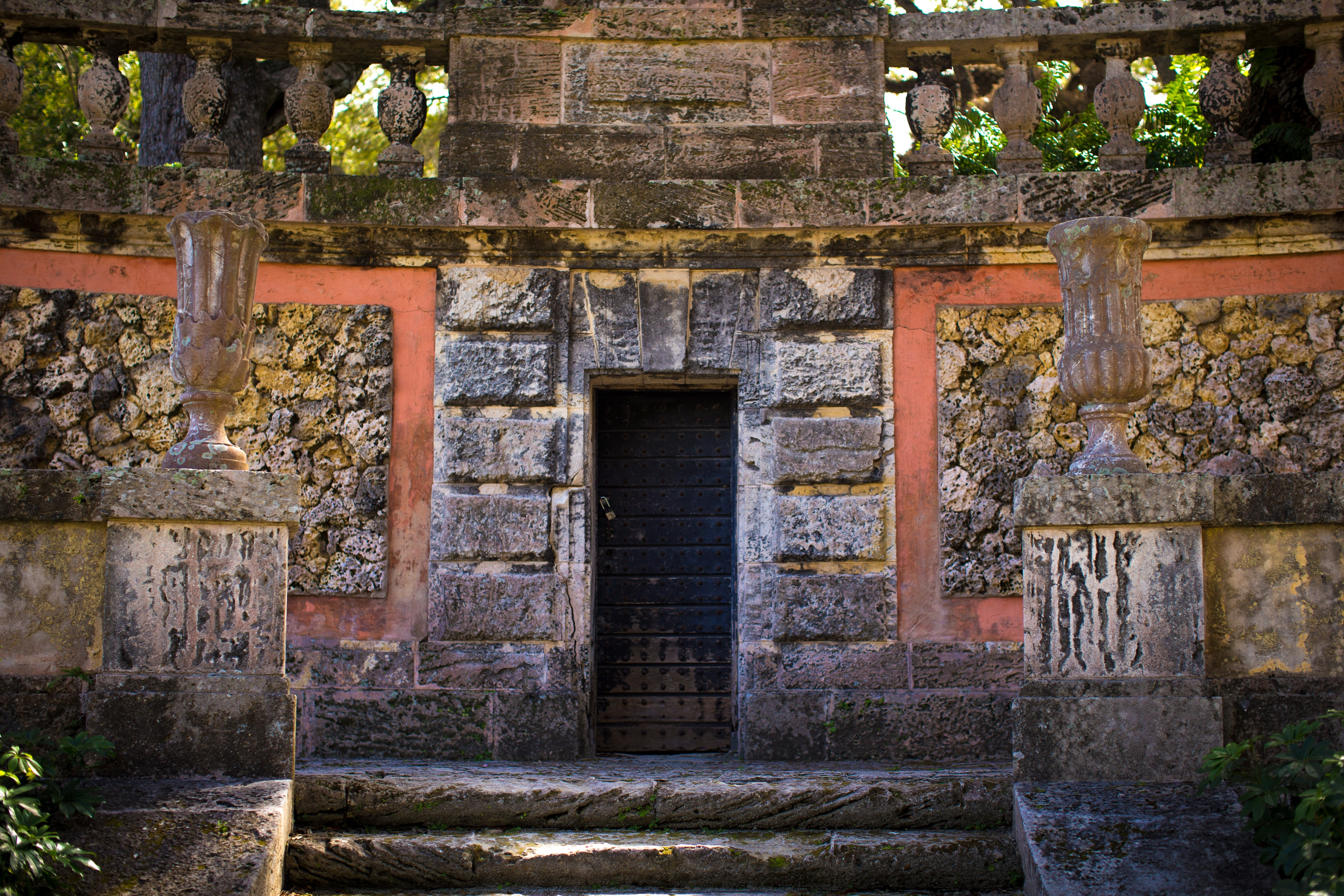 A locked door of an old block temple with steps beneath it.