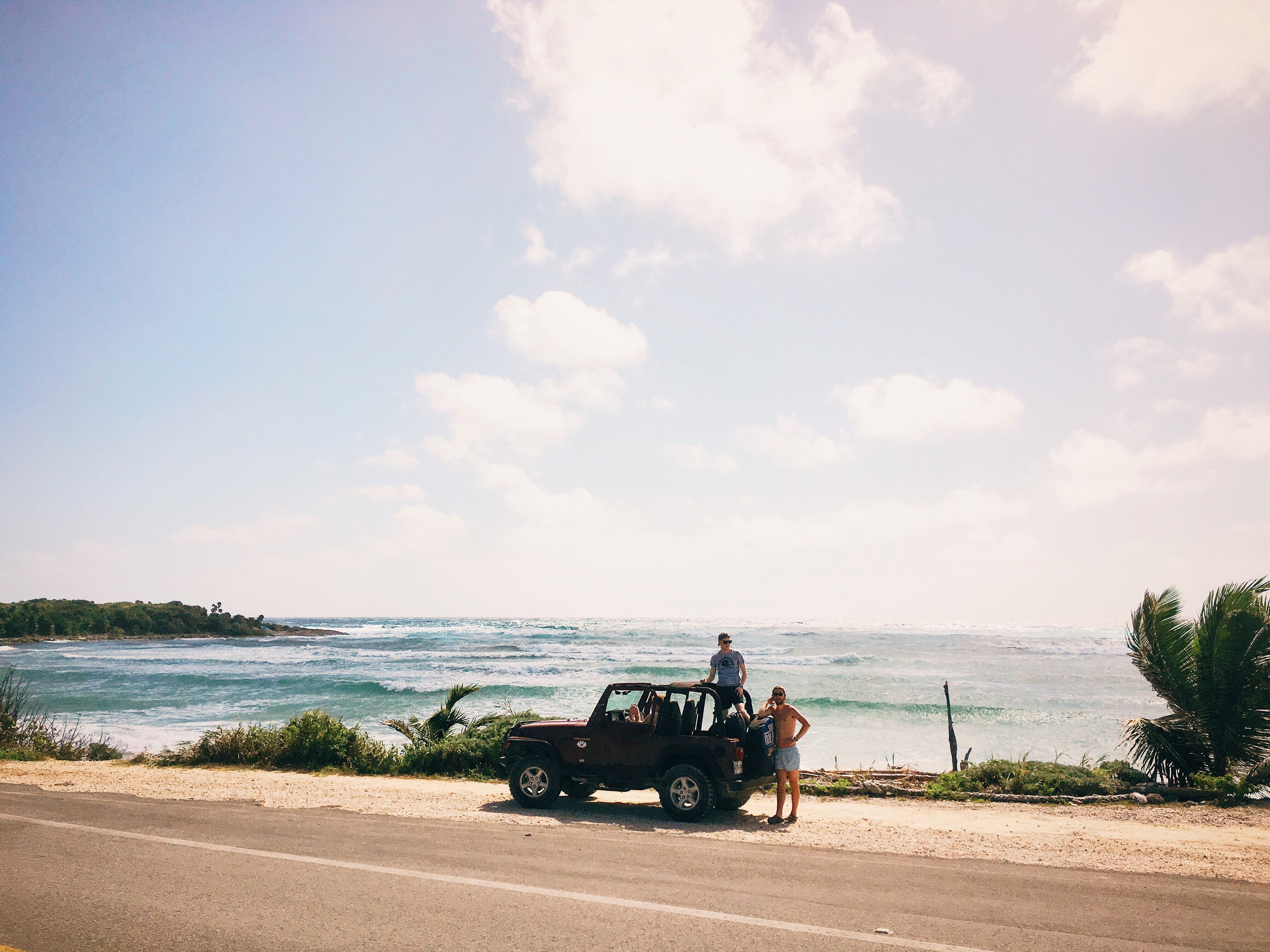 Two men by a small jeep on a coastline road at Cozumel