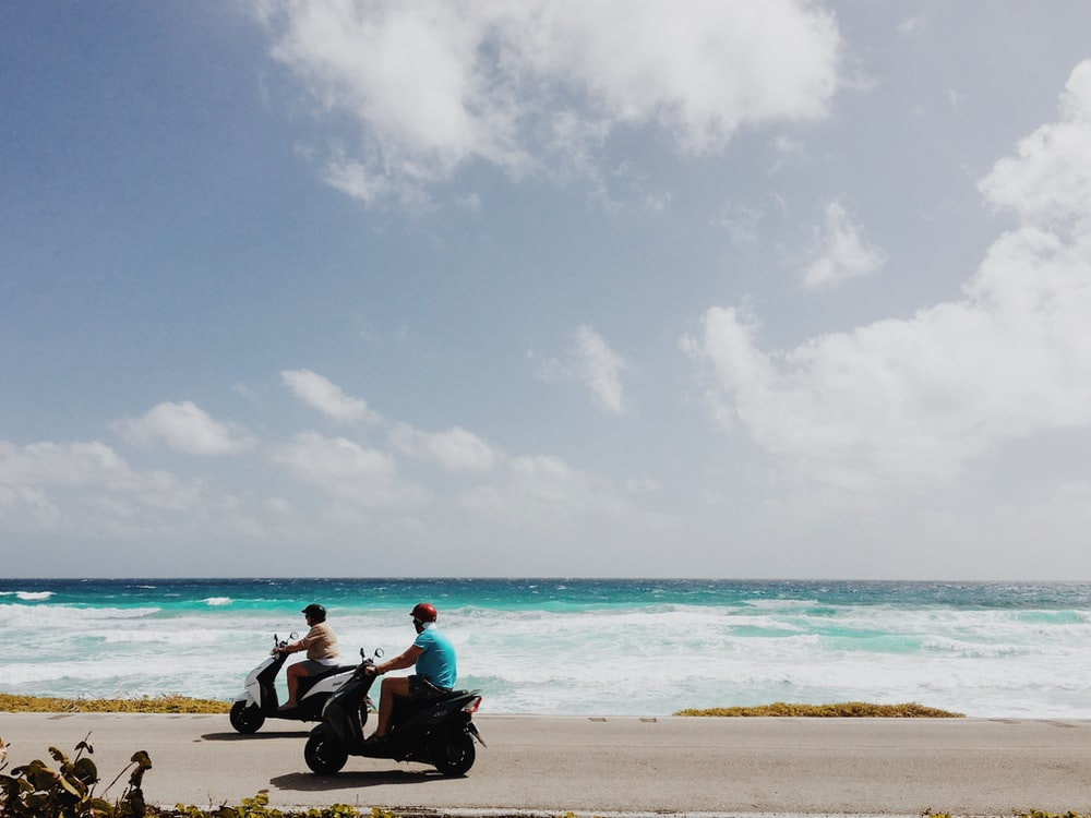 people riding motorcycle on beach side