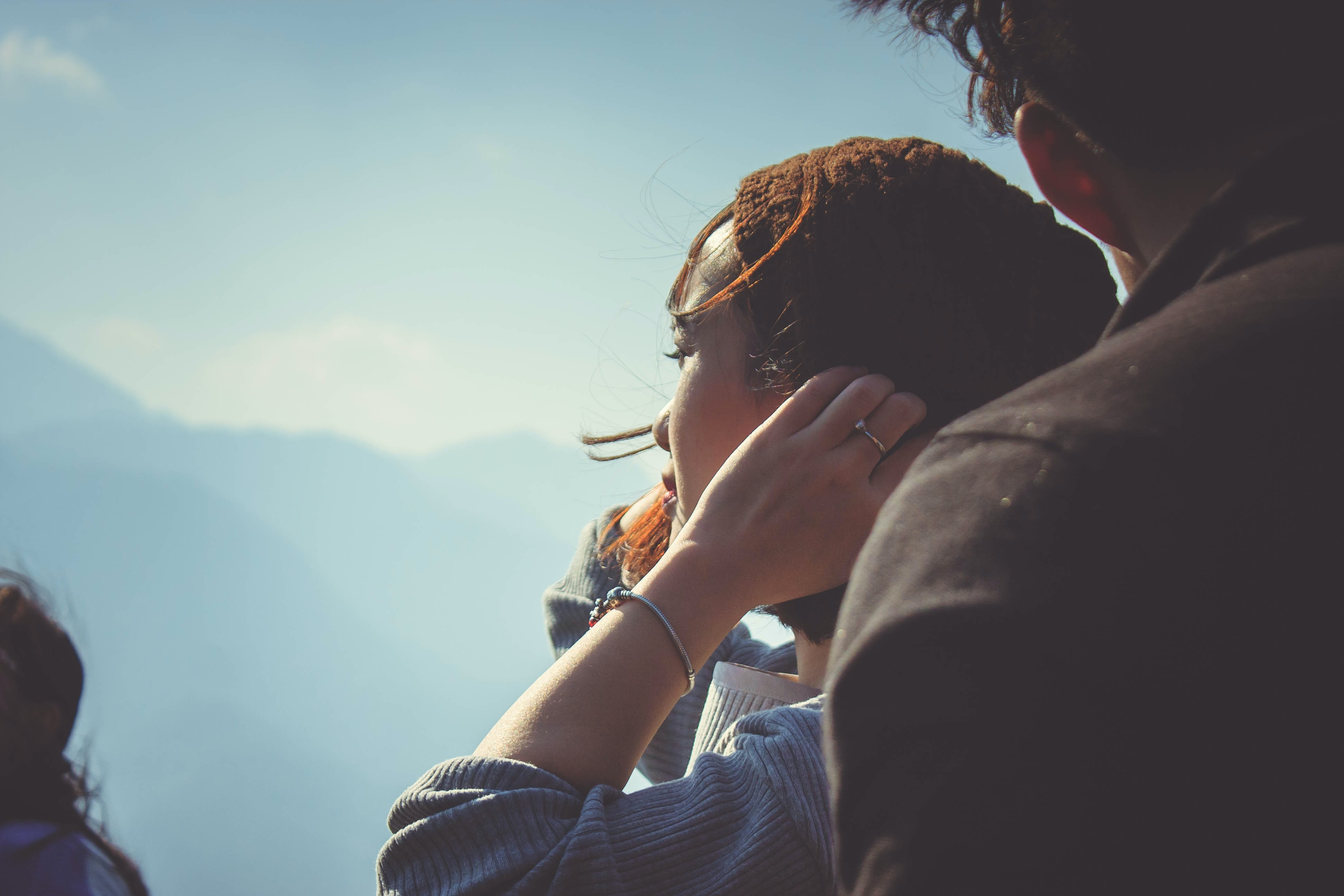 woman beside man holding her hair at daytime