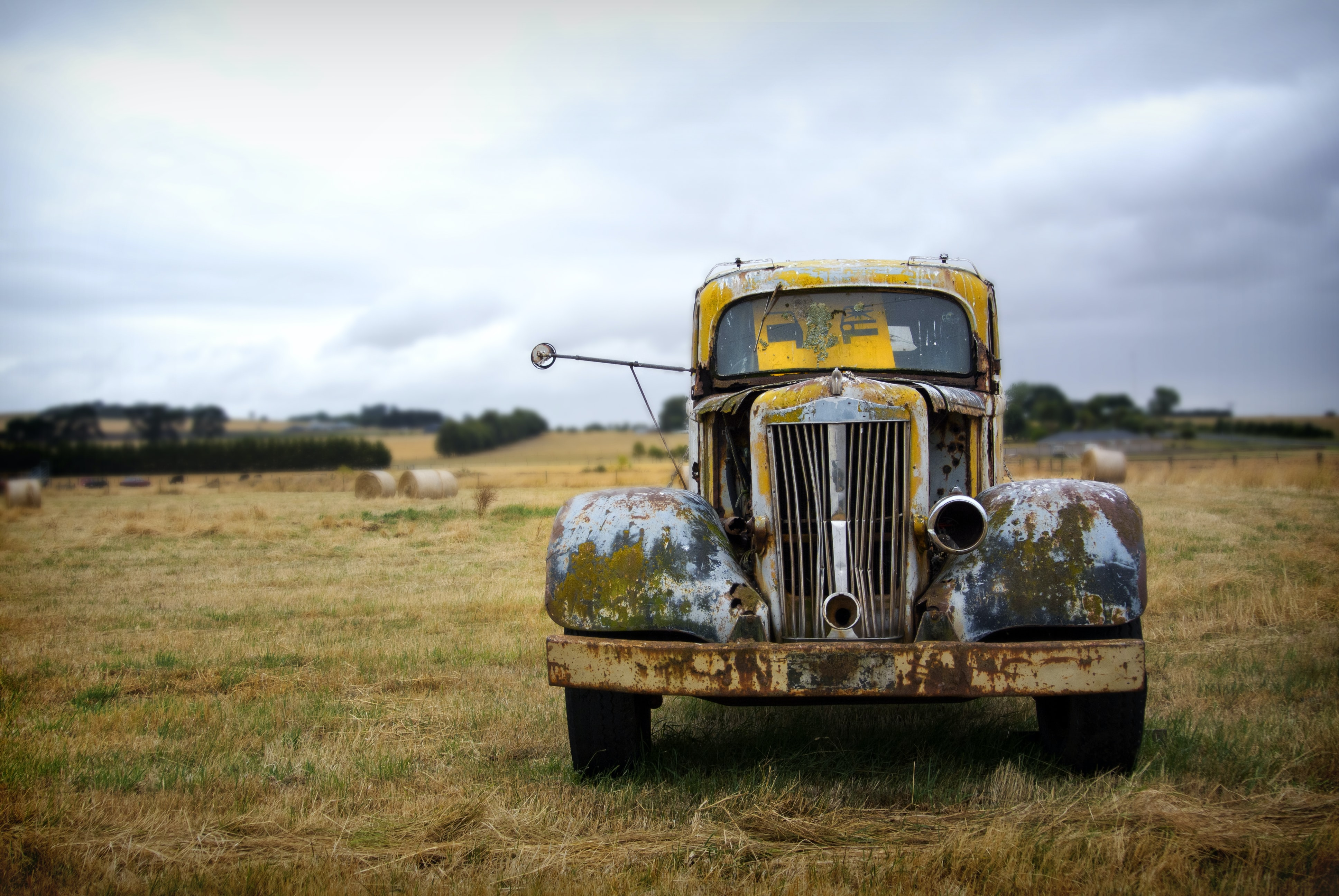 classic yellow vehicle on grass field under cloudy sky