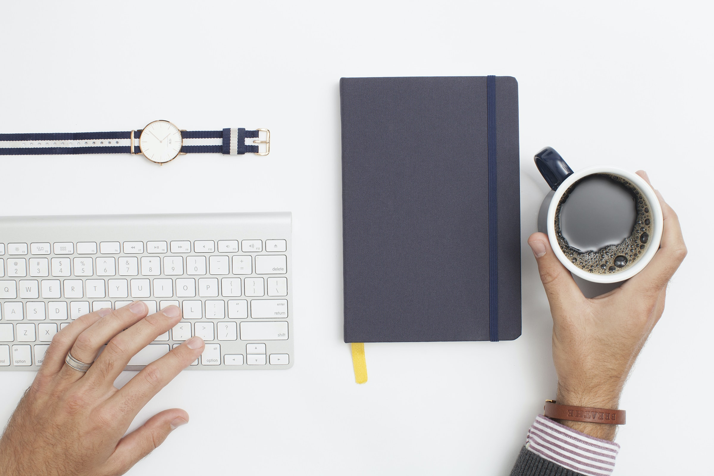 A man's hand holding a cup of coffee on a workspace with a notebook and a keyboard