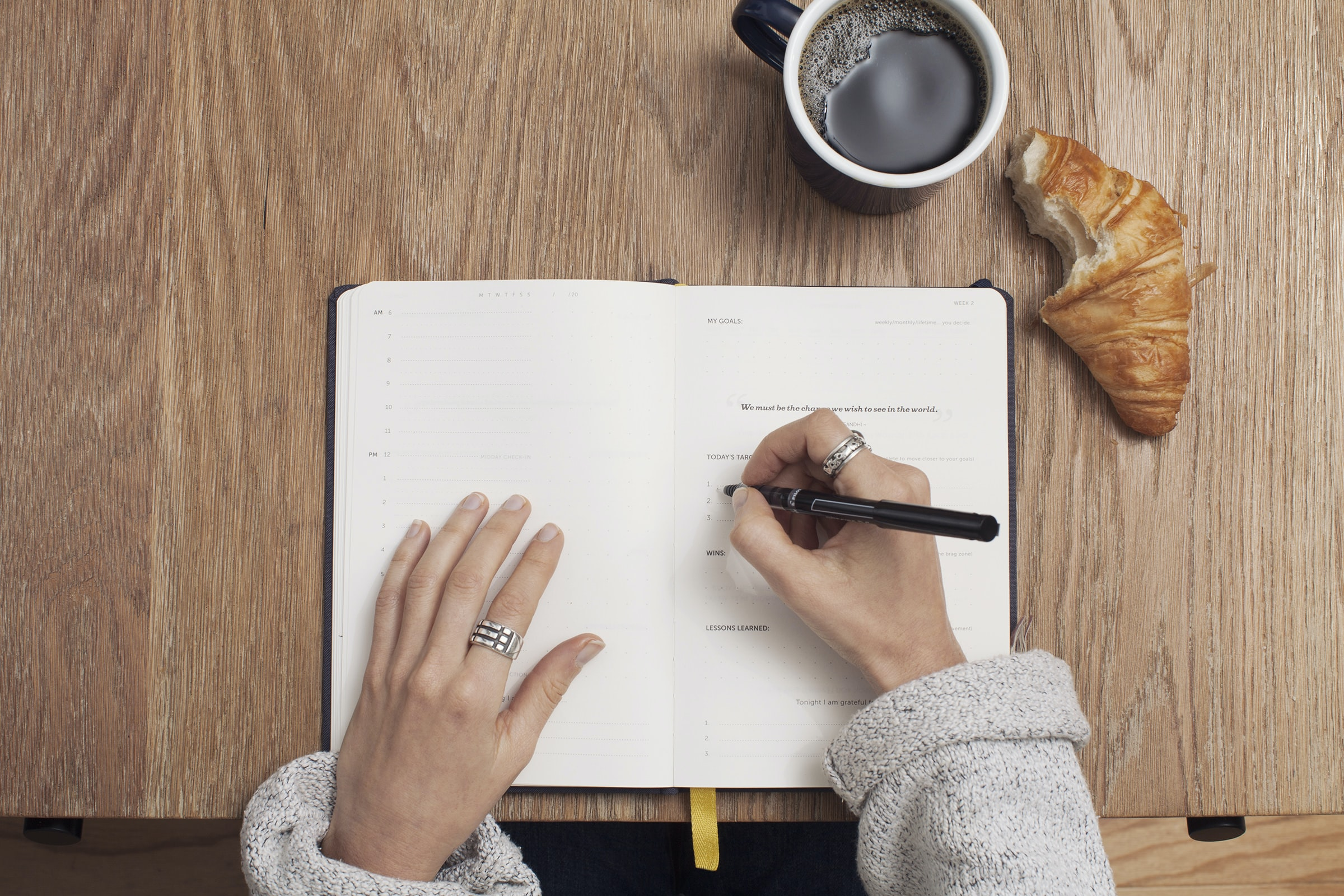 A person writing in a life planner with a coffee and a croissant on the desk