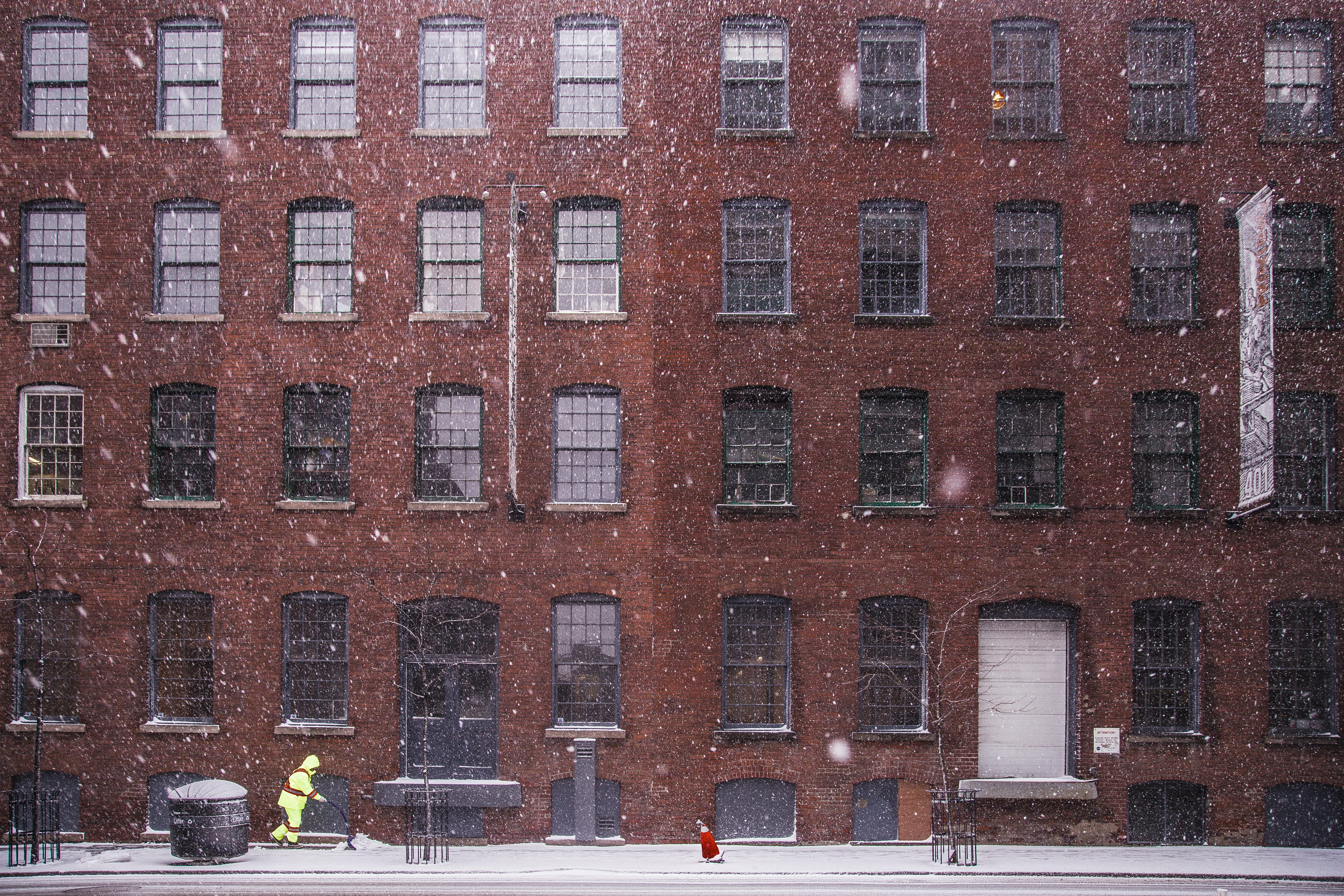 A person bundled in reflective yellow clothing shovels a sidewalk in front of a large red brick building during a snowfall