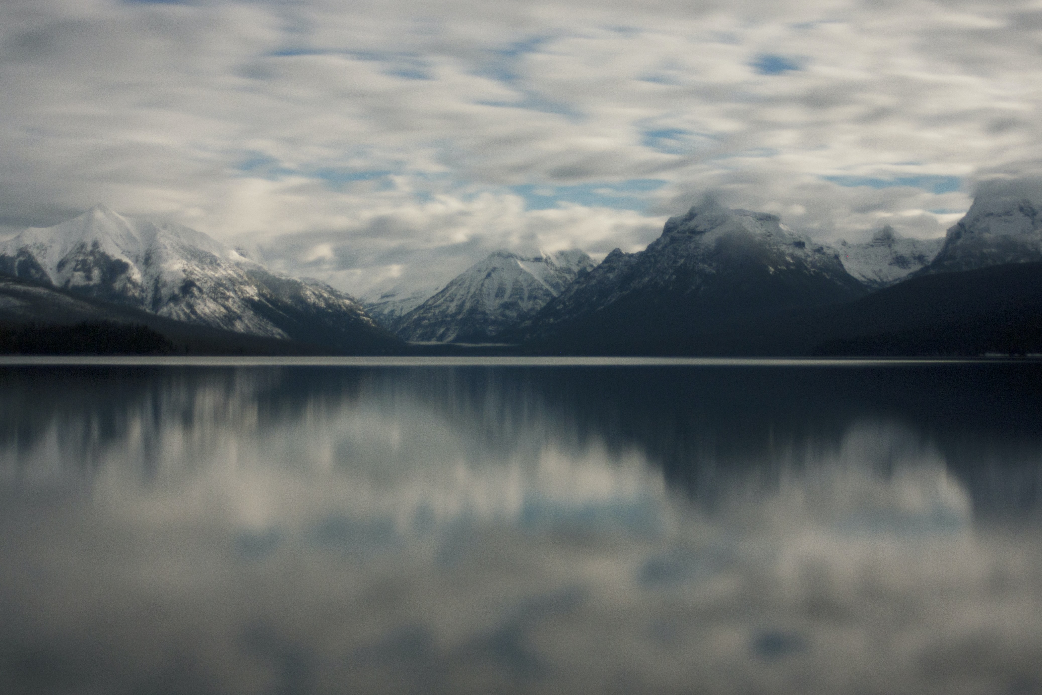 Snowcapped mountains and fluffy clouds reflected on the surface of Lake McDonald