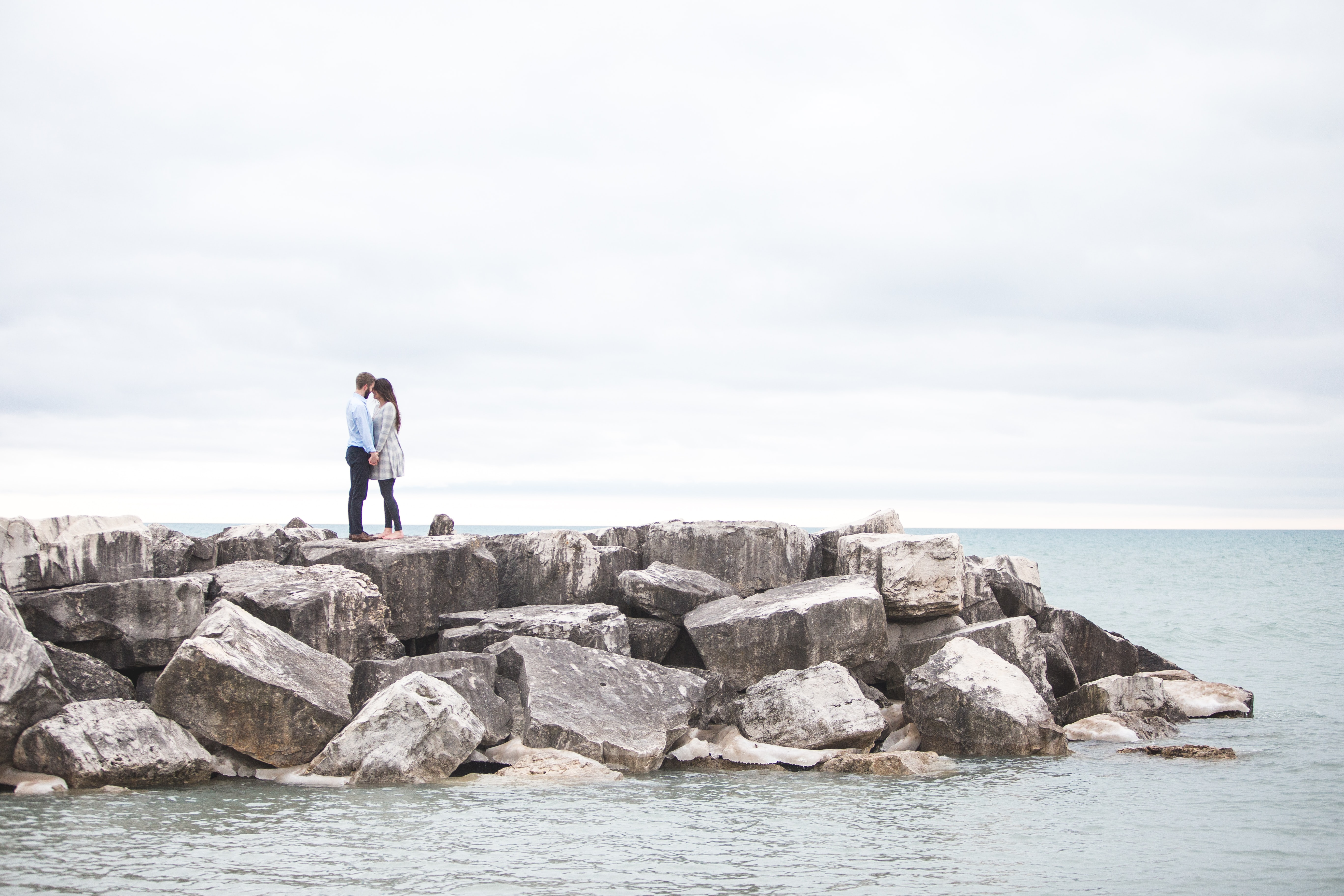 Standing atop a stone jetty on the ocean, a couple shares a tender moment