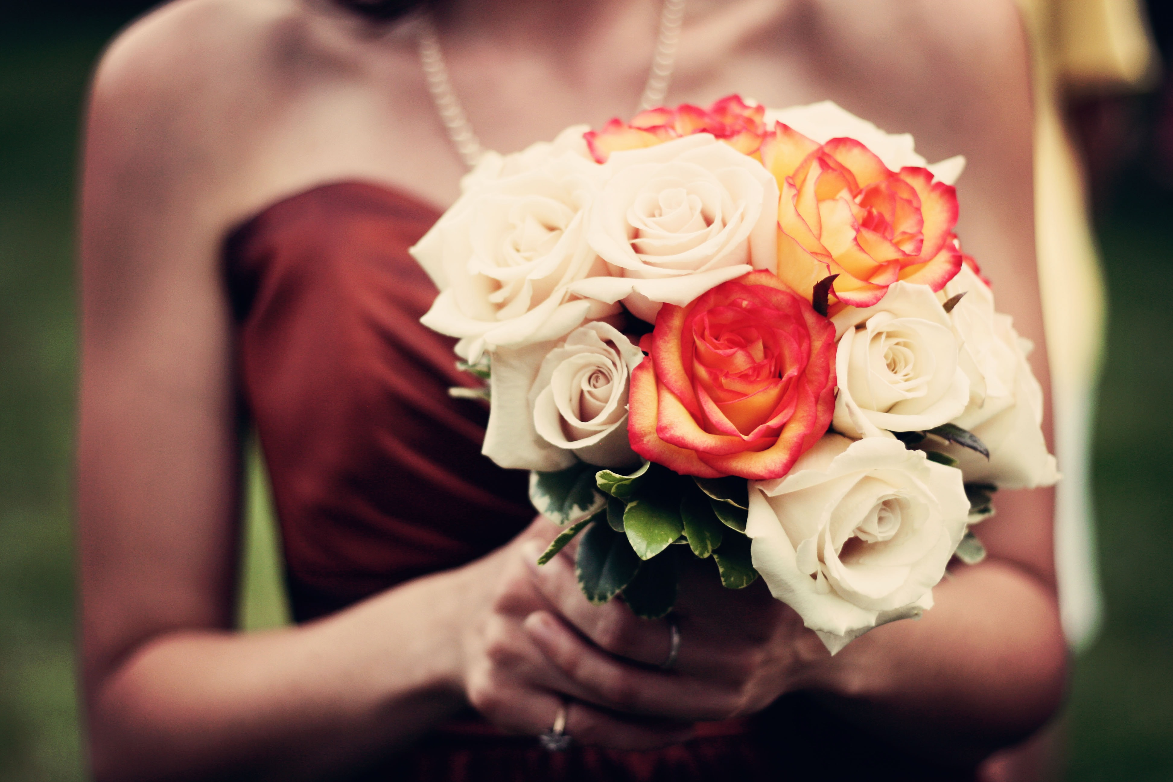 Low shot of bridesmaid holding a bouquet of roses walking down the aisle