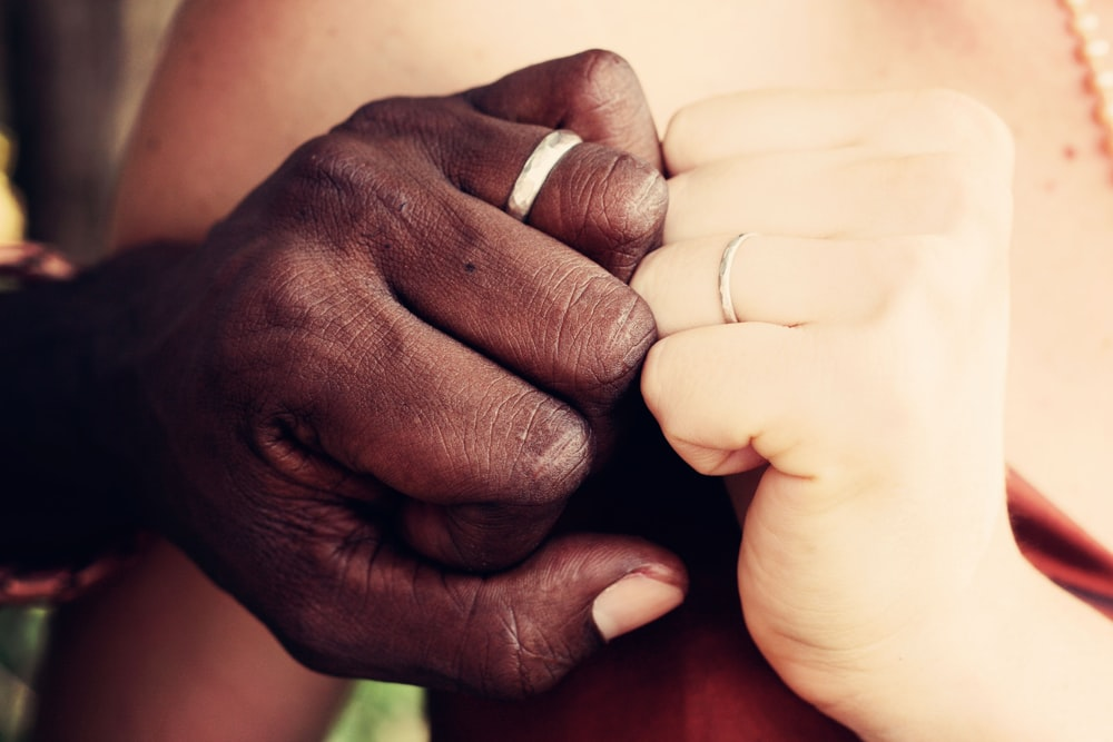 A couple holds their fists against one another, showing off their wedding bands