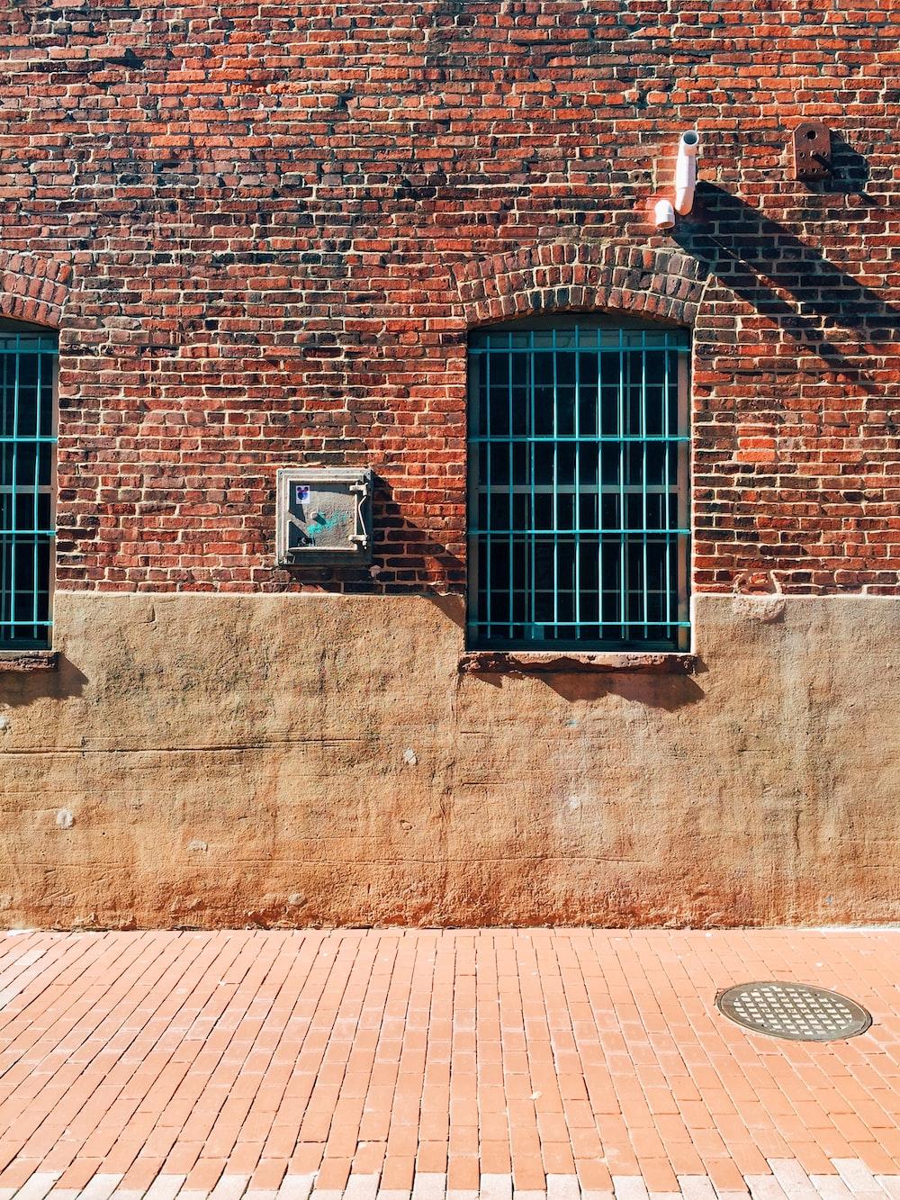 black metal window on brown brick wall