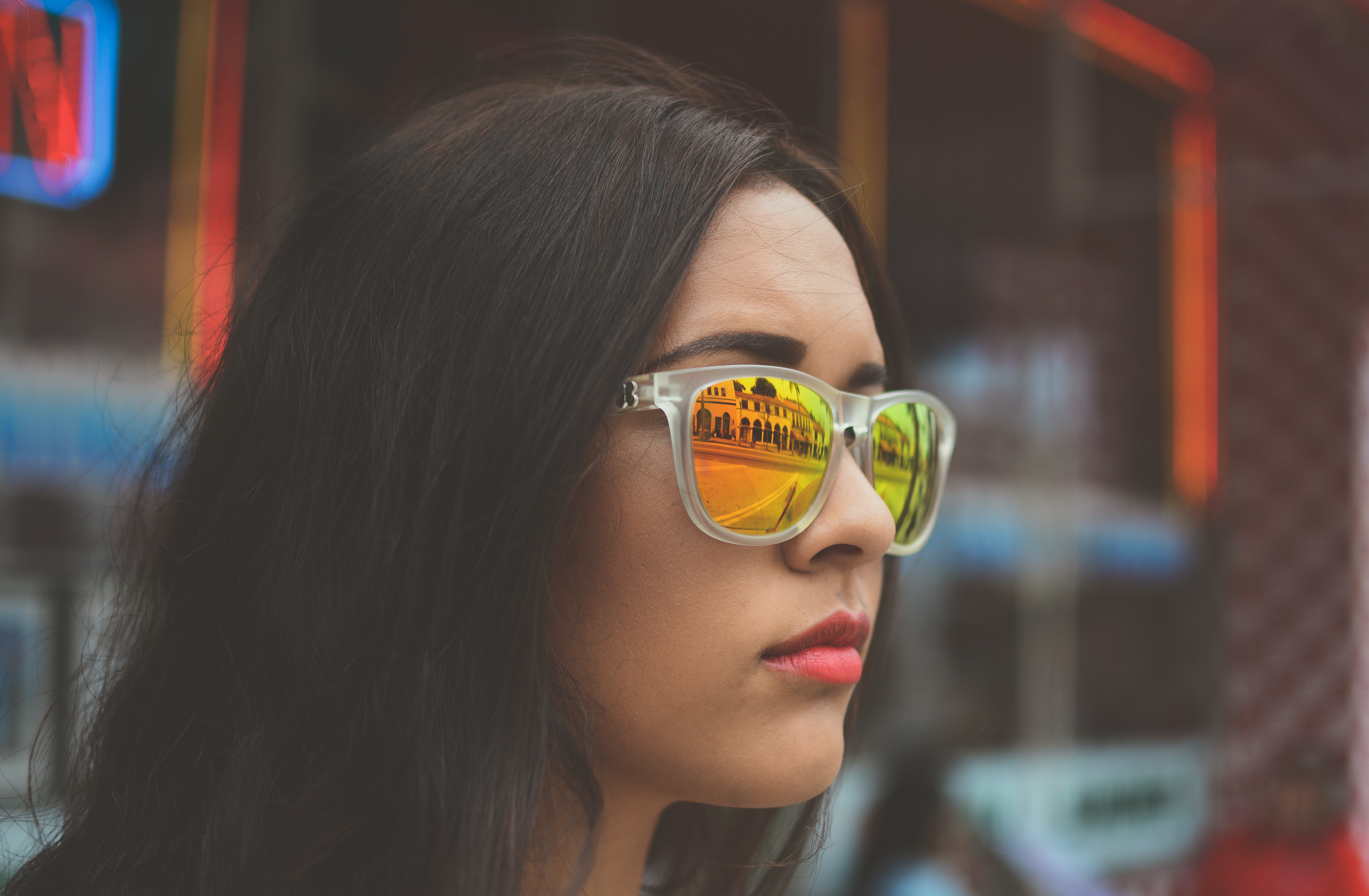 Woman wearing reflective sunglasses looking out at a city street