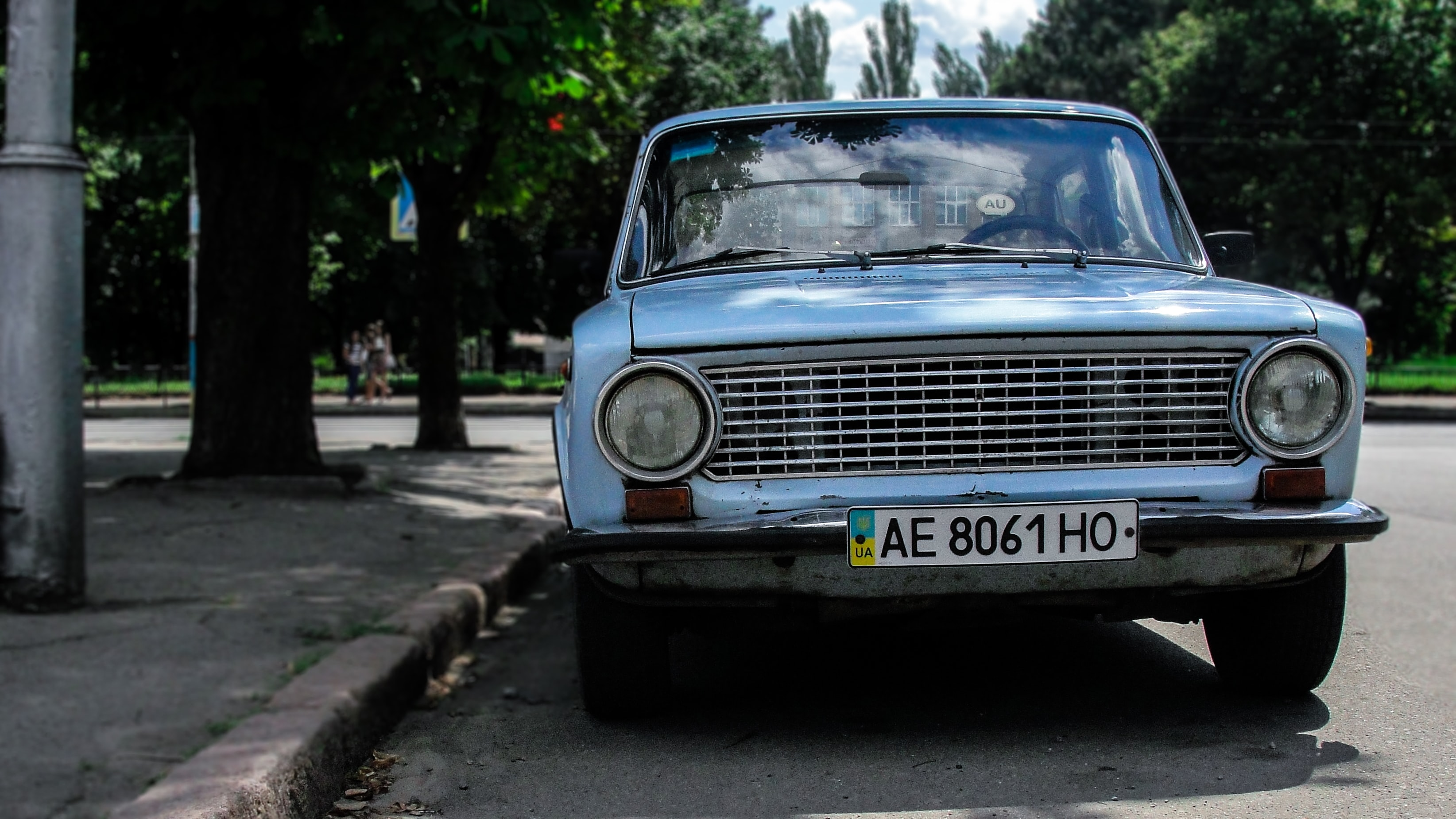 Vintage pale blue car parked on pavement on sunny day  in Kryvyi Rih
