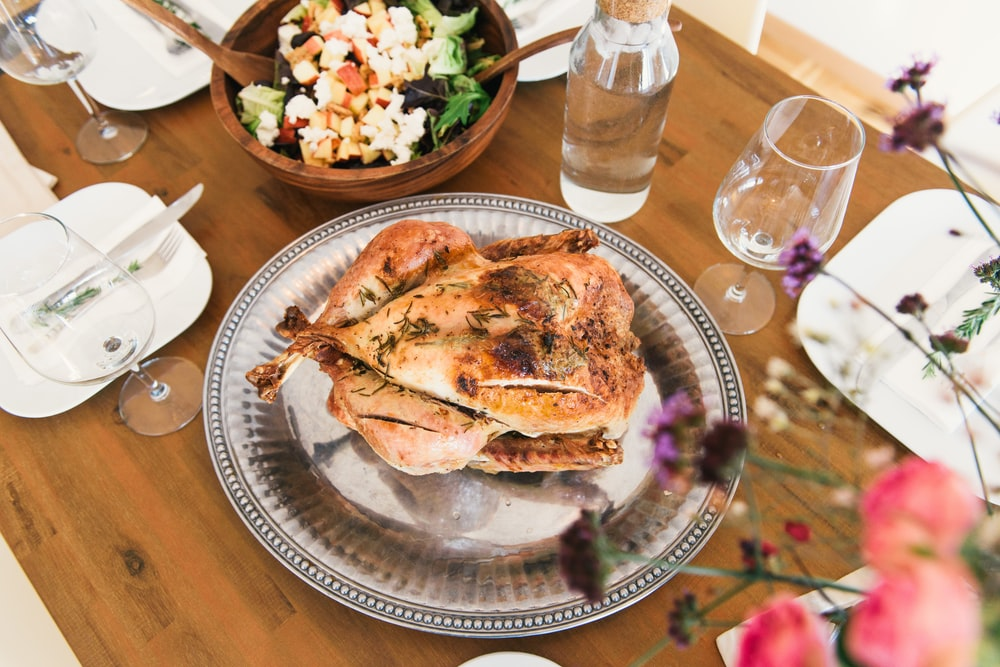 Roast chicken dinner with herbs on a platter with a bowl of salad