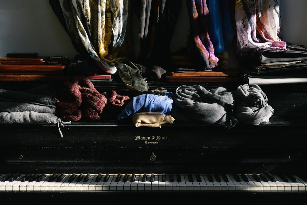 assorted clothes on top of piano