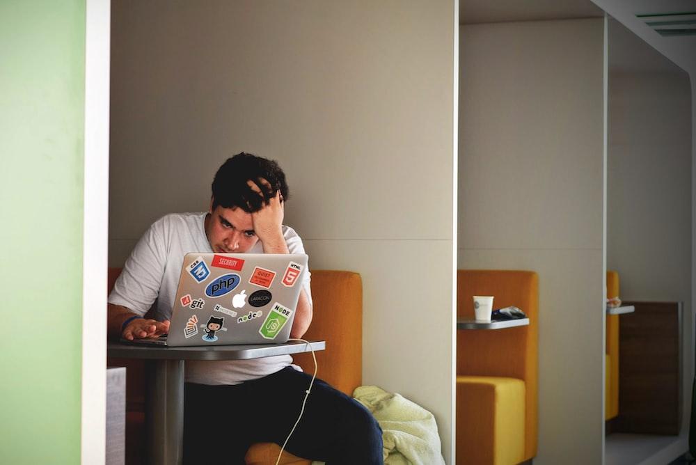 man wearing white top using MacBook