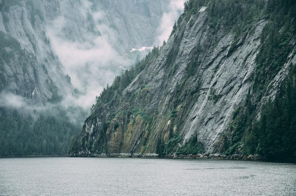 grey rock cliff near body of water
