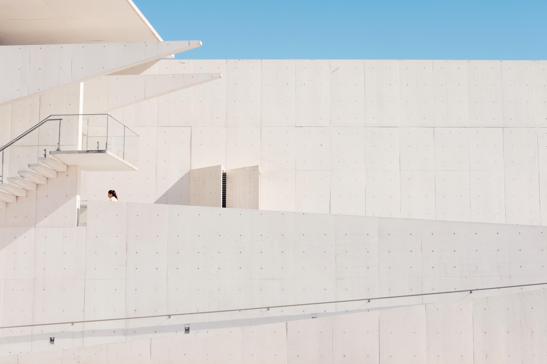 A woman near a stairway behind a white concrete facade
