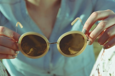 woman holding round sunglasses during daytime sunglass zoom background
