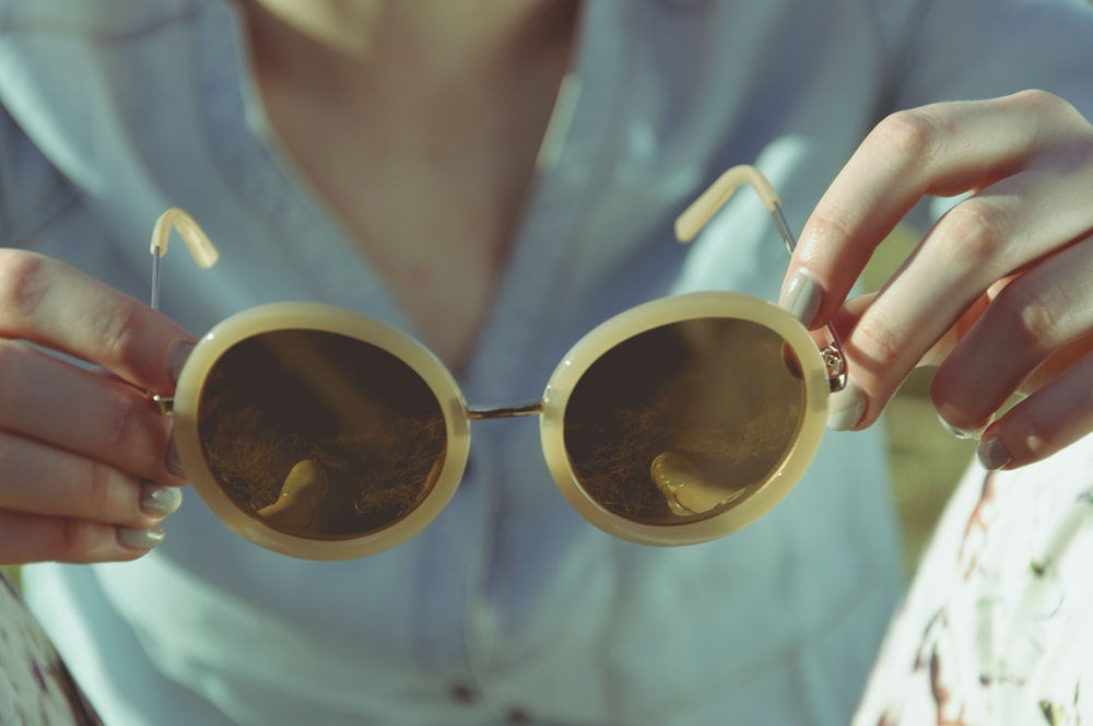 woman holding round sunglasses during daytime