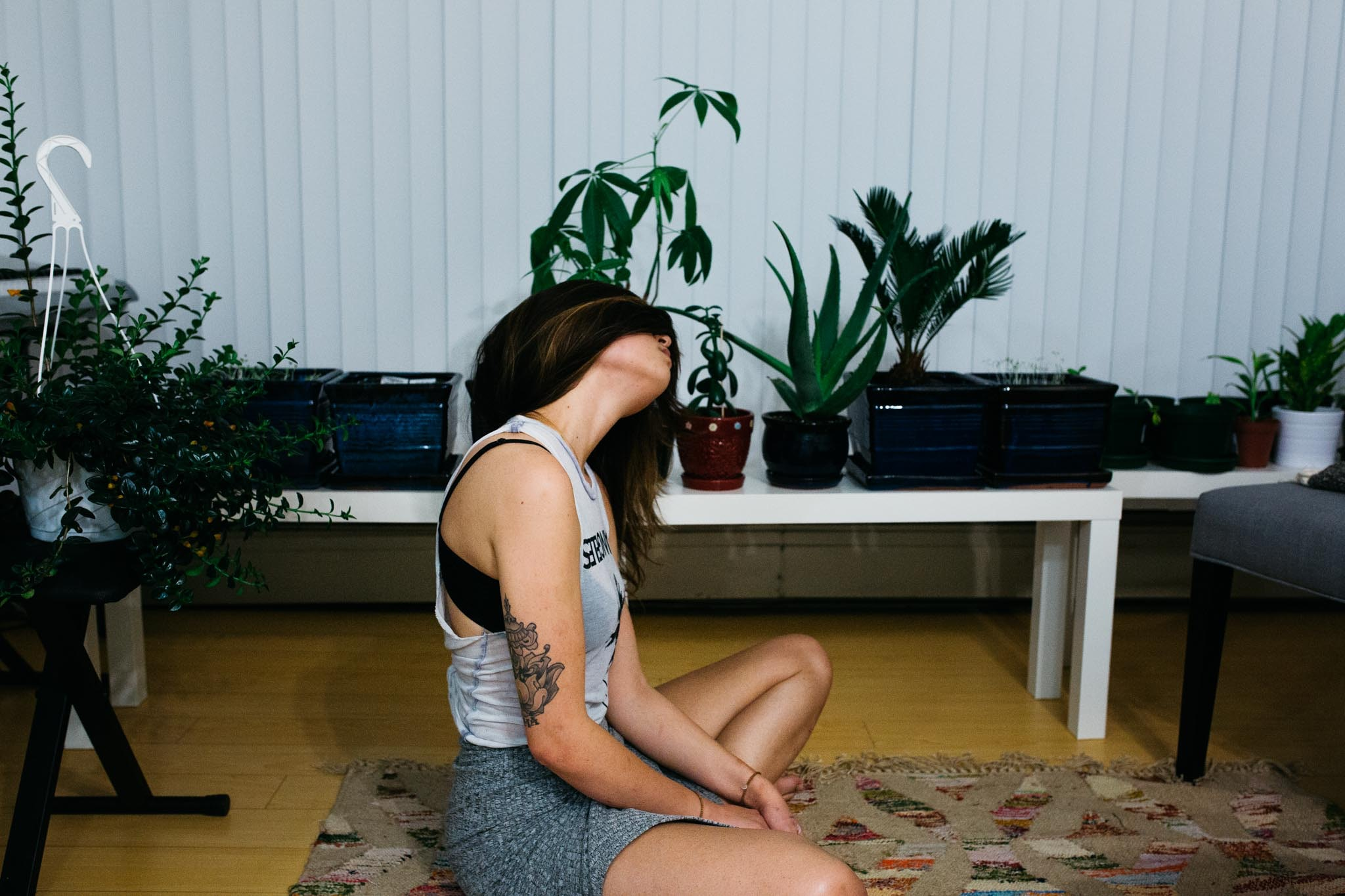 A brunette woman doing yoga in her living room that is filled with plants