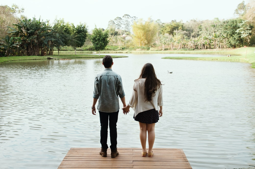 man and woman standing on dock