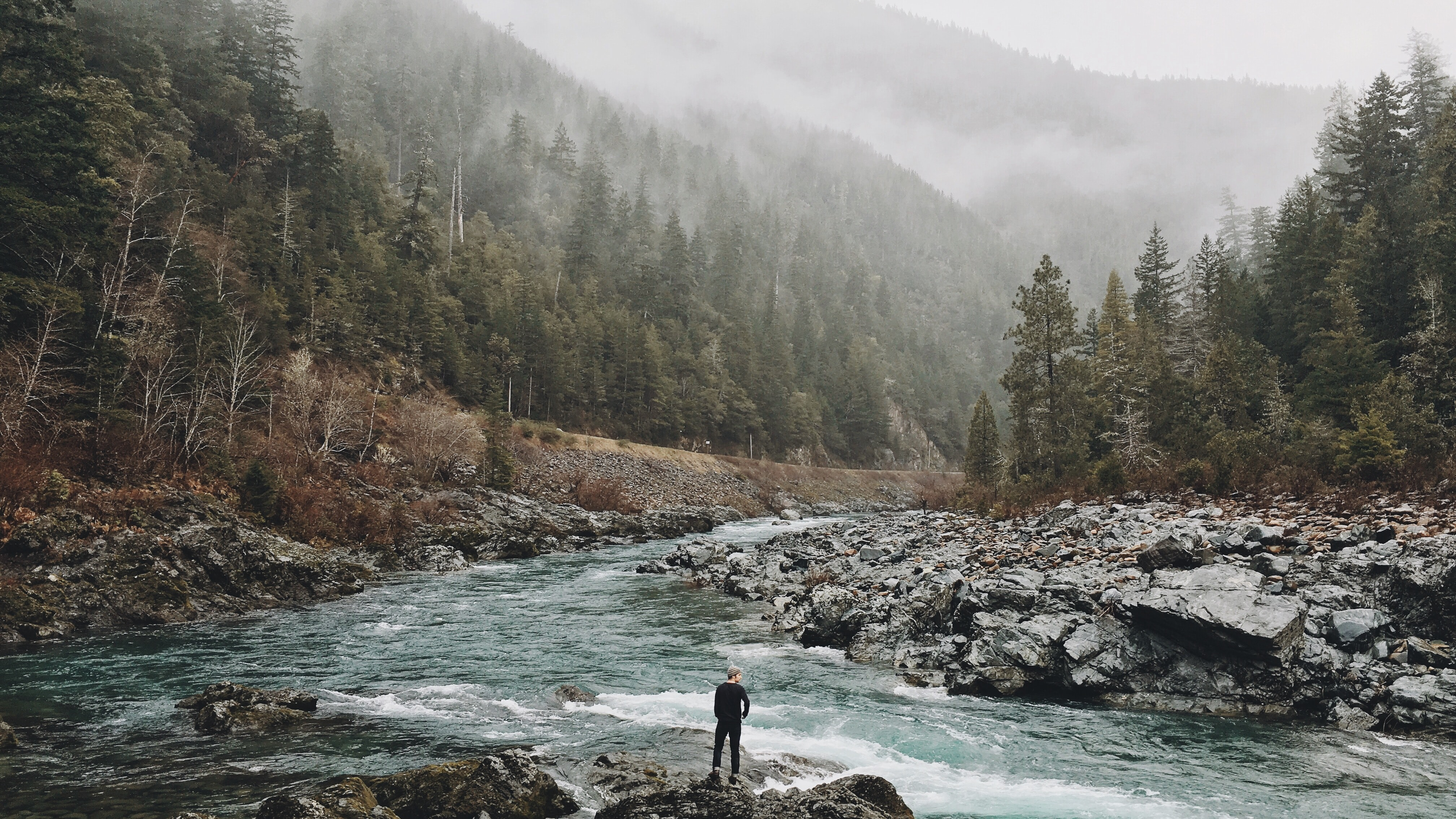 A man standing on jagged rocks in a fast-flowing river in the wilderness