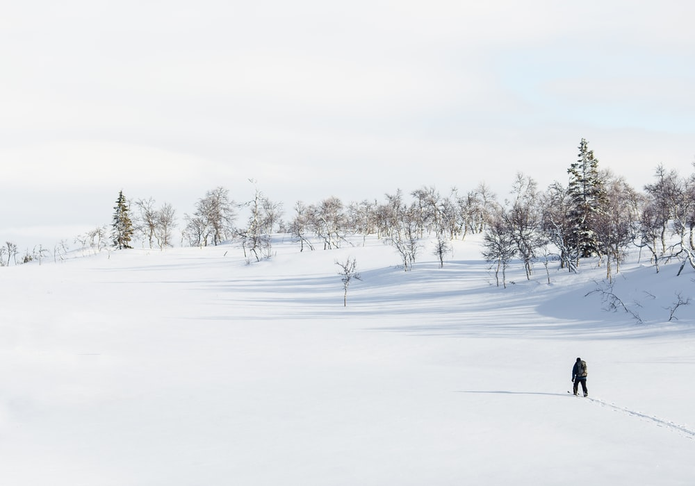 man walking on snow field during daytime