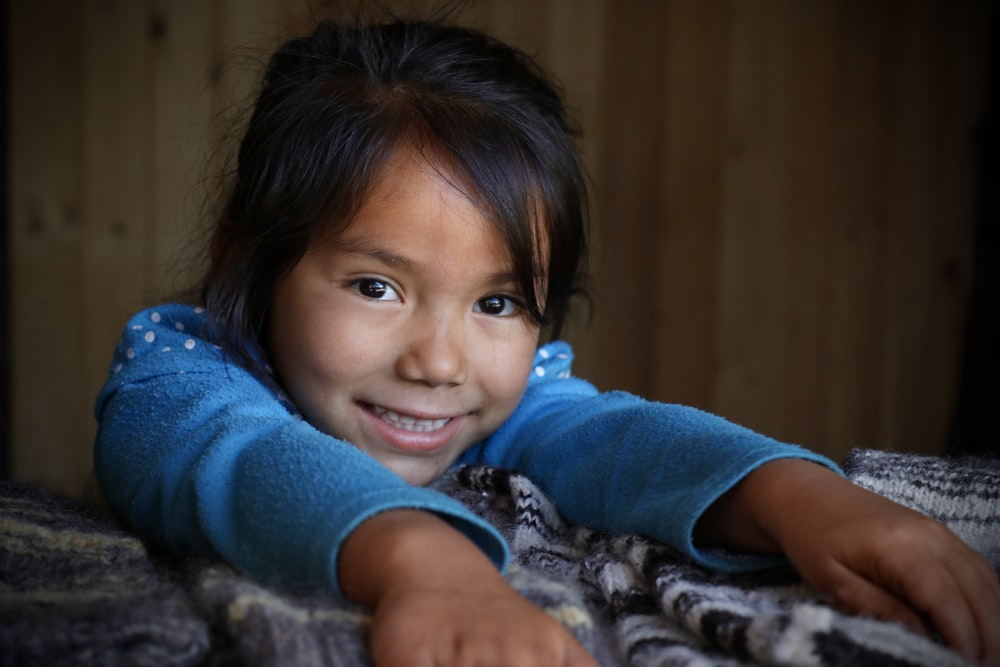 girl wearing blue sweater with hands on gray bedspread