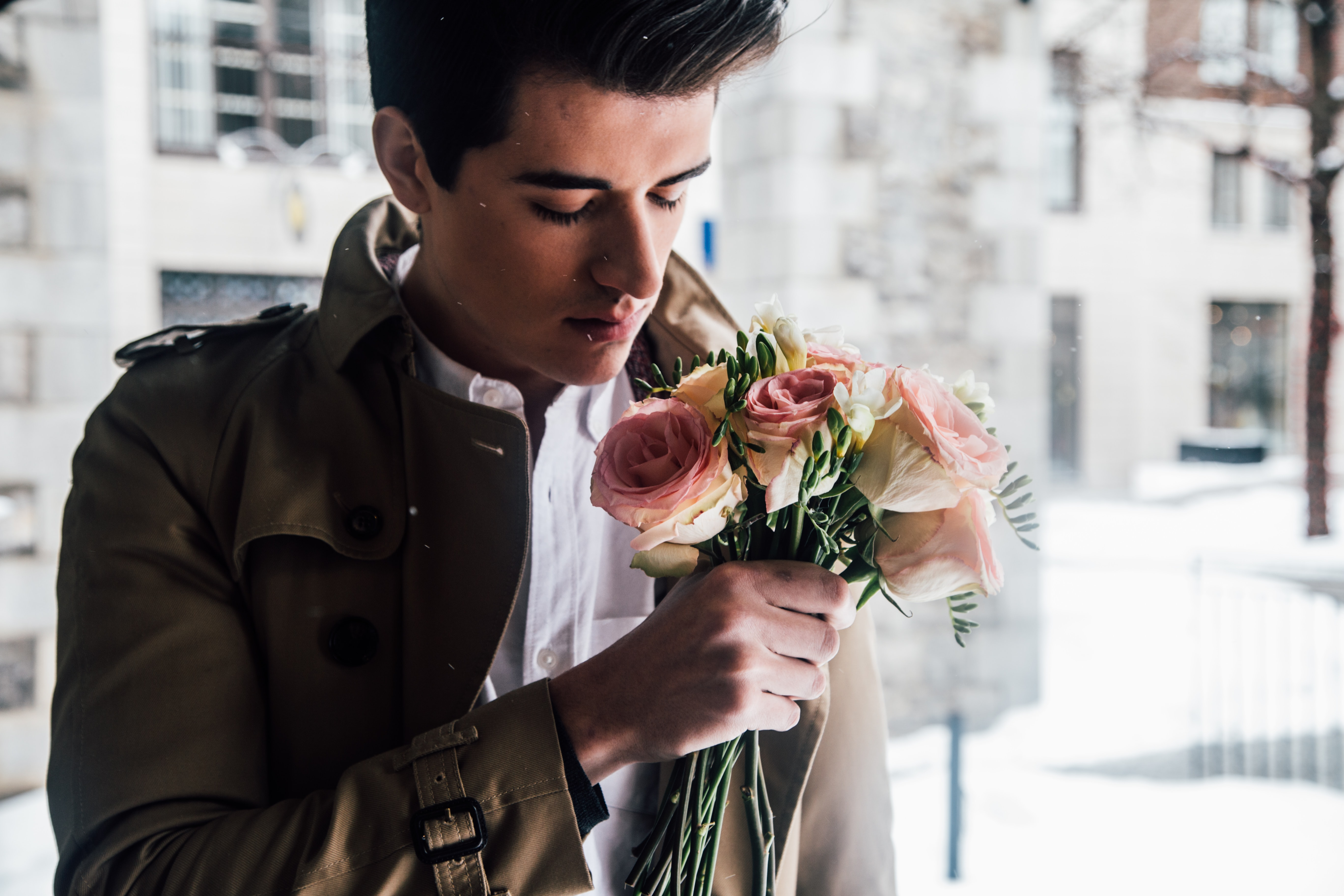 Trendy young man in a trenchcoat holds a romantic bouquet of flowers