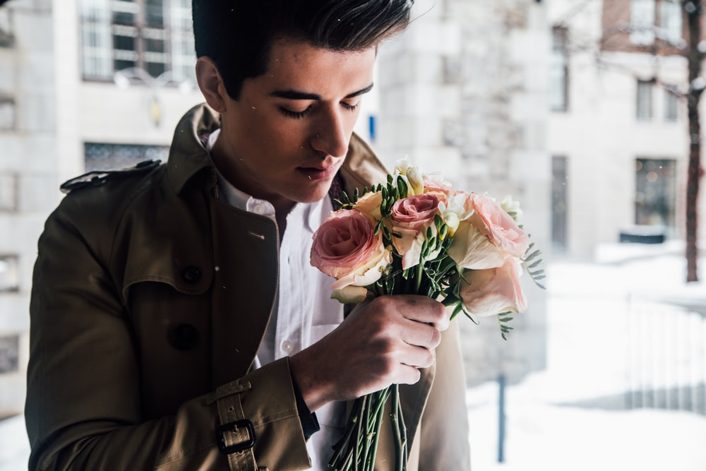 man holding pink roses Cute First Date Ideas
