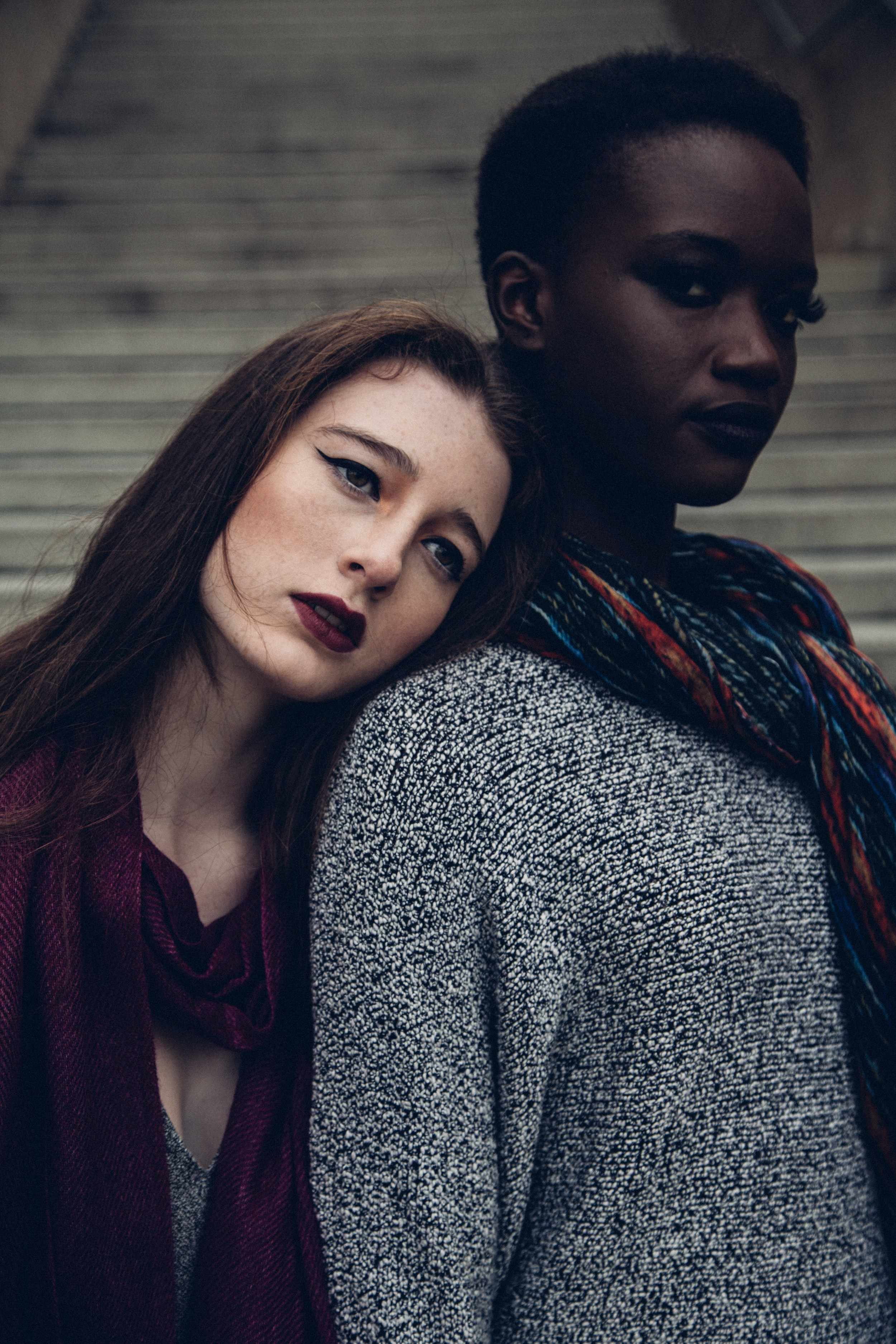 woman leaning her head to another woman during daytime