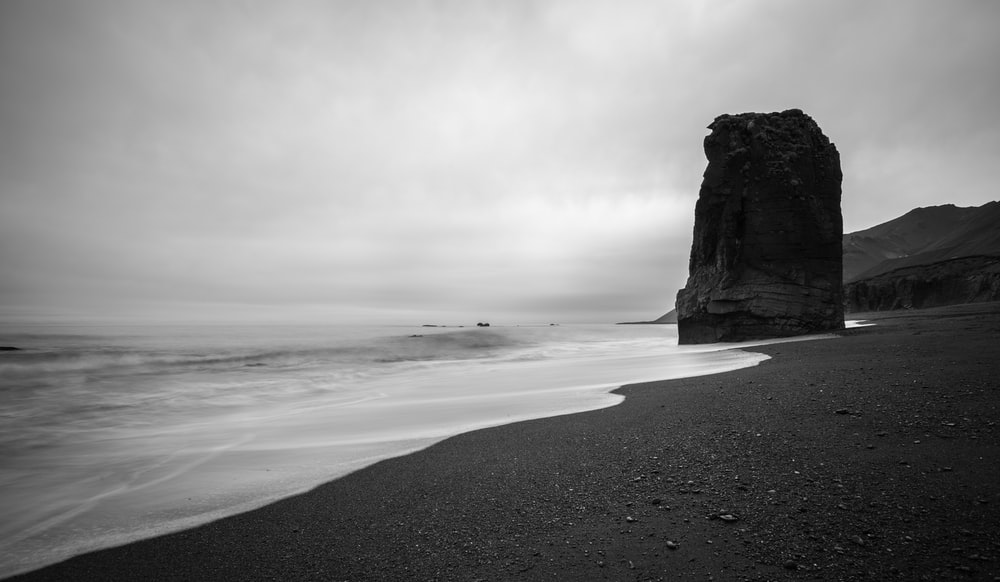large rock on shore grayscale photography