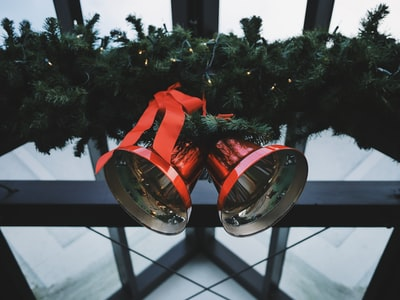 two red steel bells beside green Christmas decoration