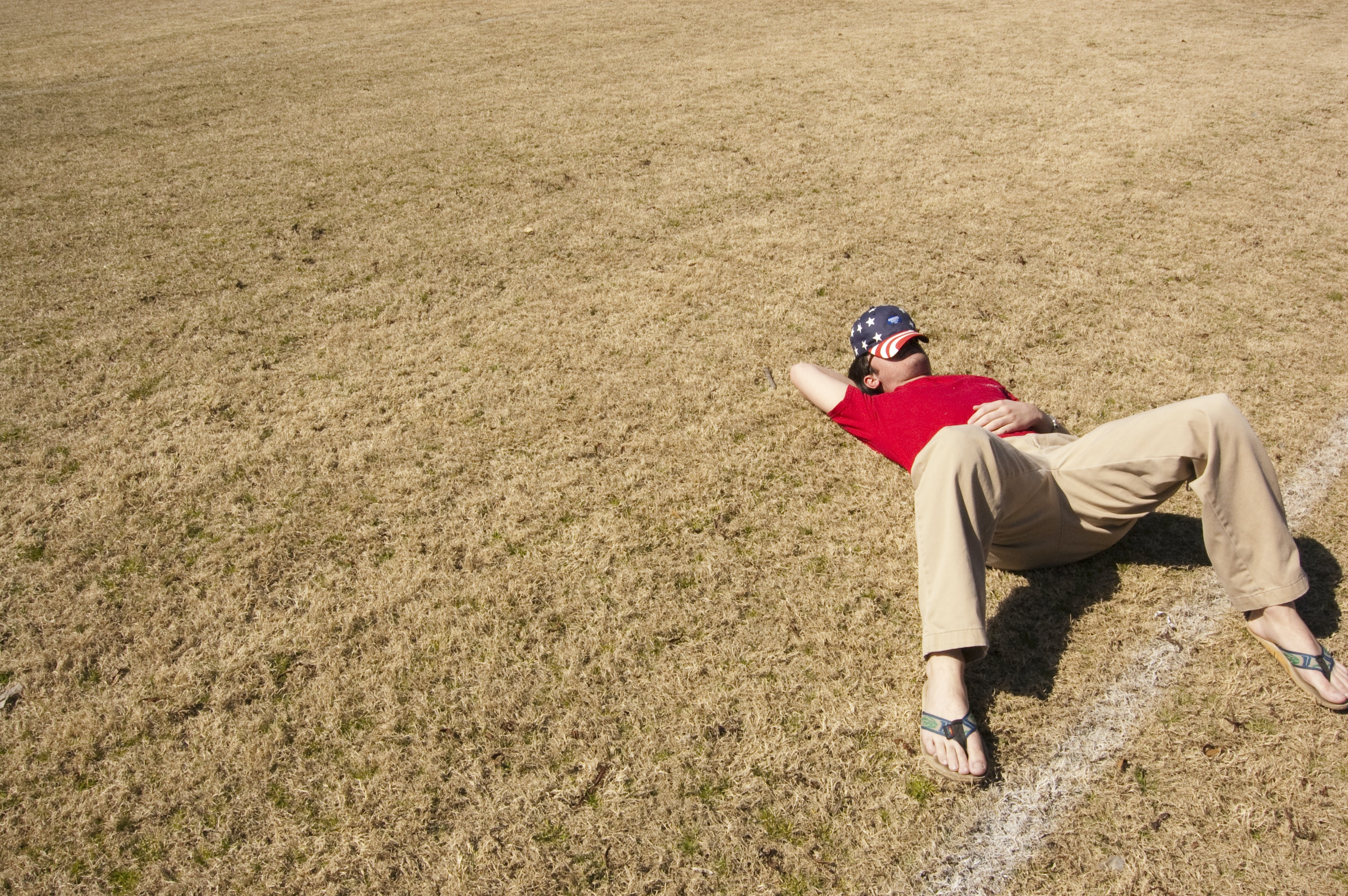 man in red top lying on lawn field during daytime