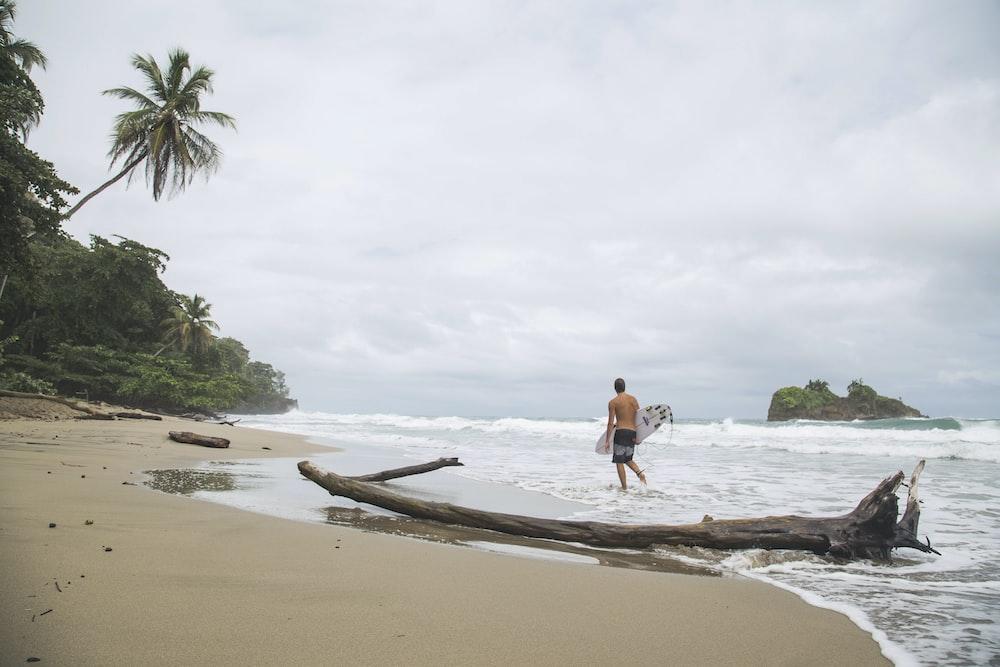 woman in blue bikini walking on beach during daytime