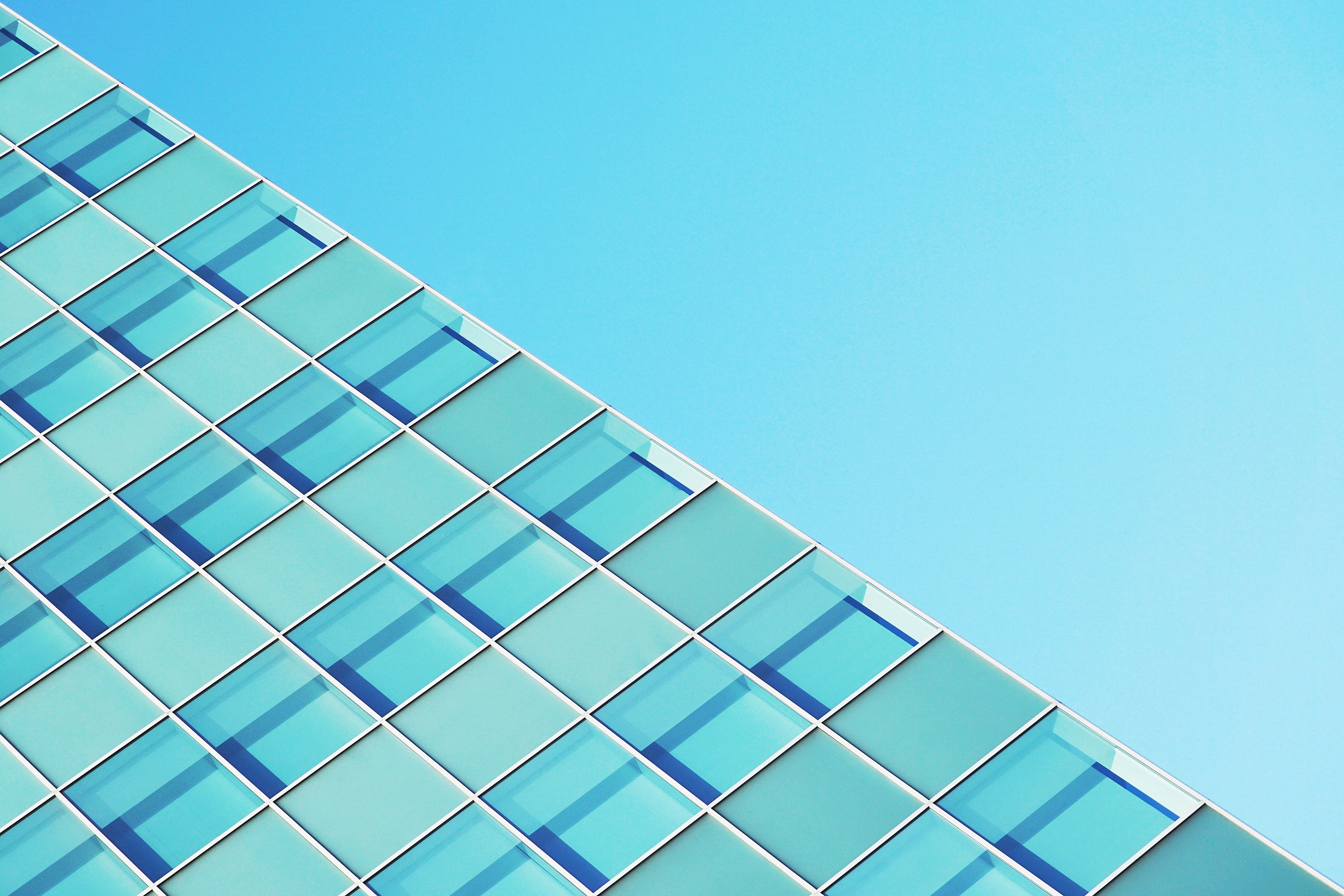 The edge of a glass-covered facade against a blue sky