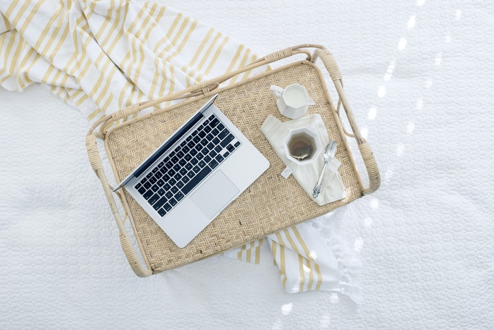 gray laptop computer on beige wicker chair