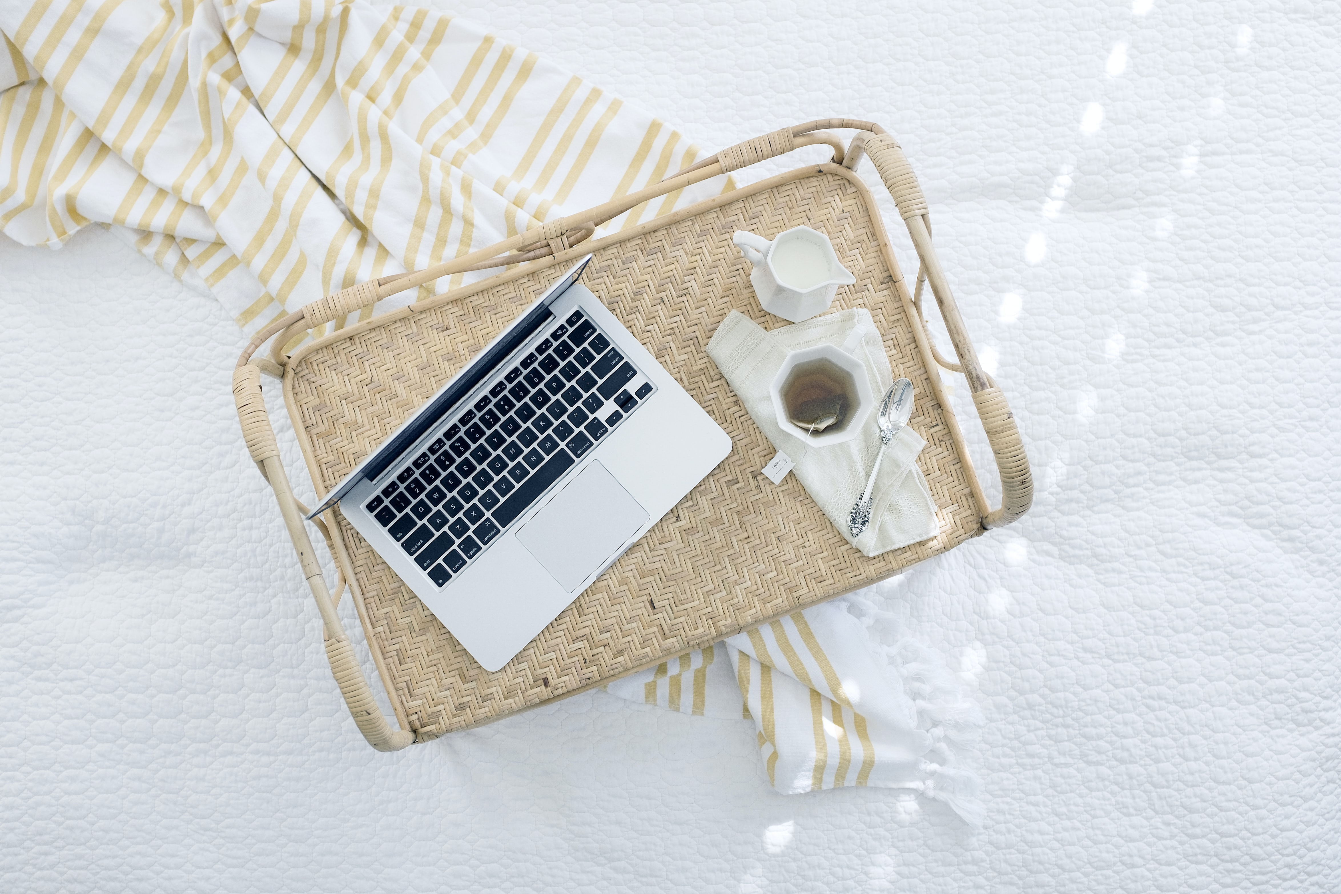 A laptop and a cup of tea with milk on a wicker tray