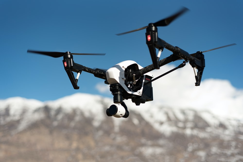 white and black quadcopter hovering under blue skies