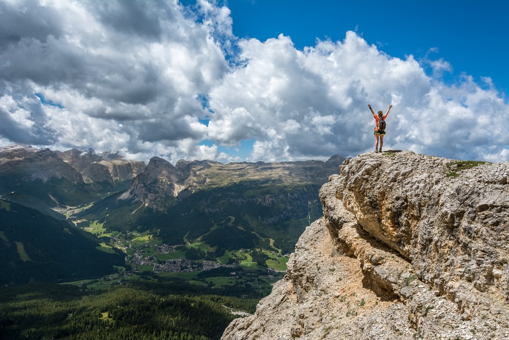 A person throwing their hands up in the air on the edge of a tall jagged rock