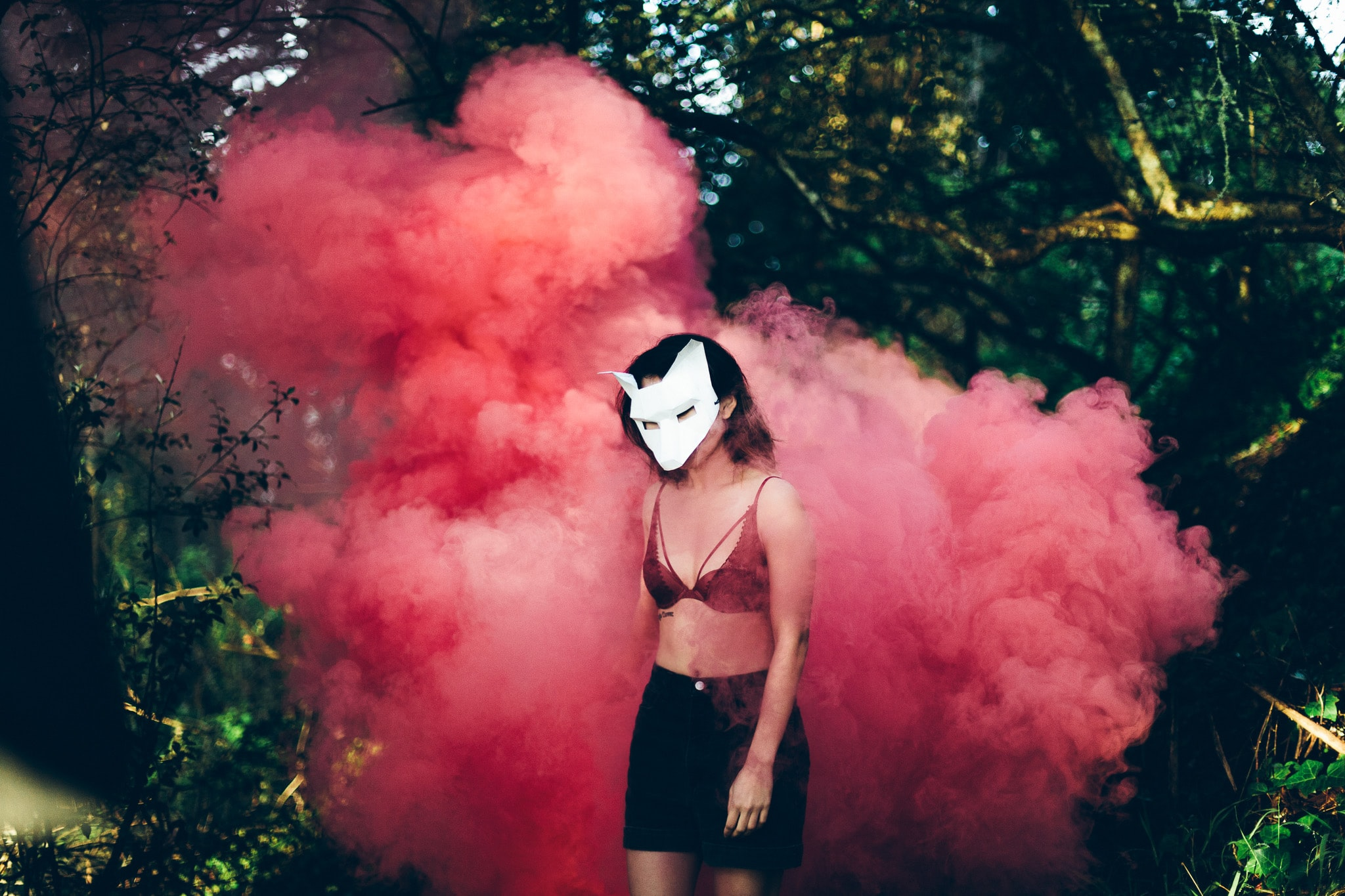 A shirtless woman in a paper wolf mask standing in front of a cloud of pink smoke in a forest environment