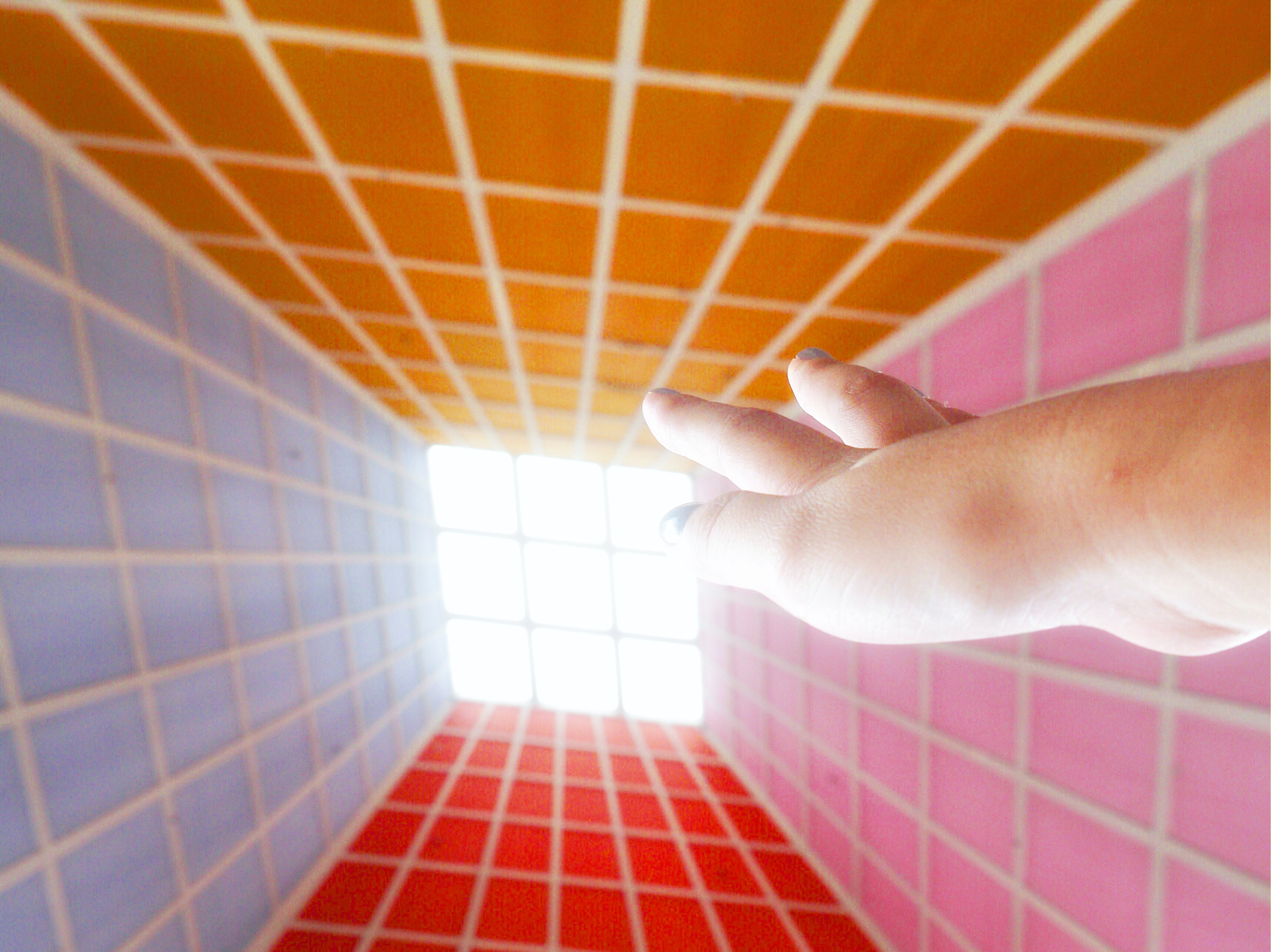 A hand reaching up to a sky-lit window in a room surrounded by four different color walls with box patterns.
