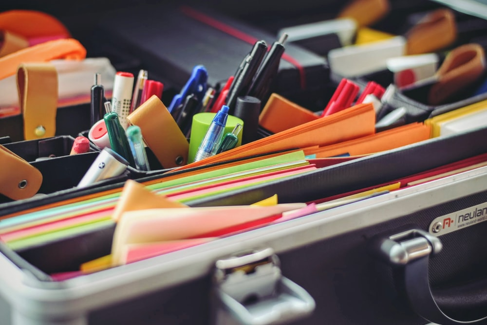 assorted pen and colored papers in organizer case